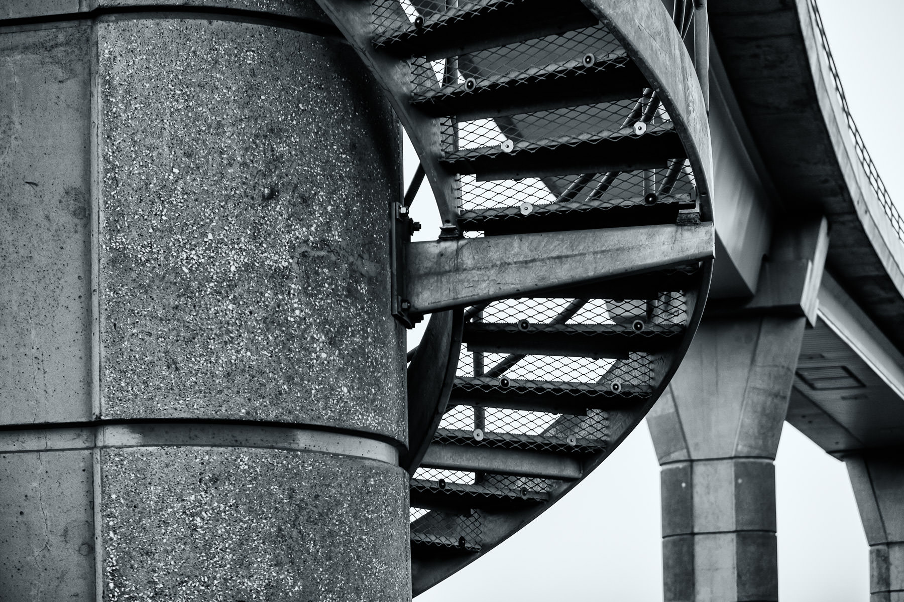 A maintenance stairway wraps around a support column for the Skylink train at DFW International Airport, Texas.