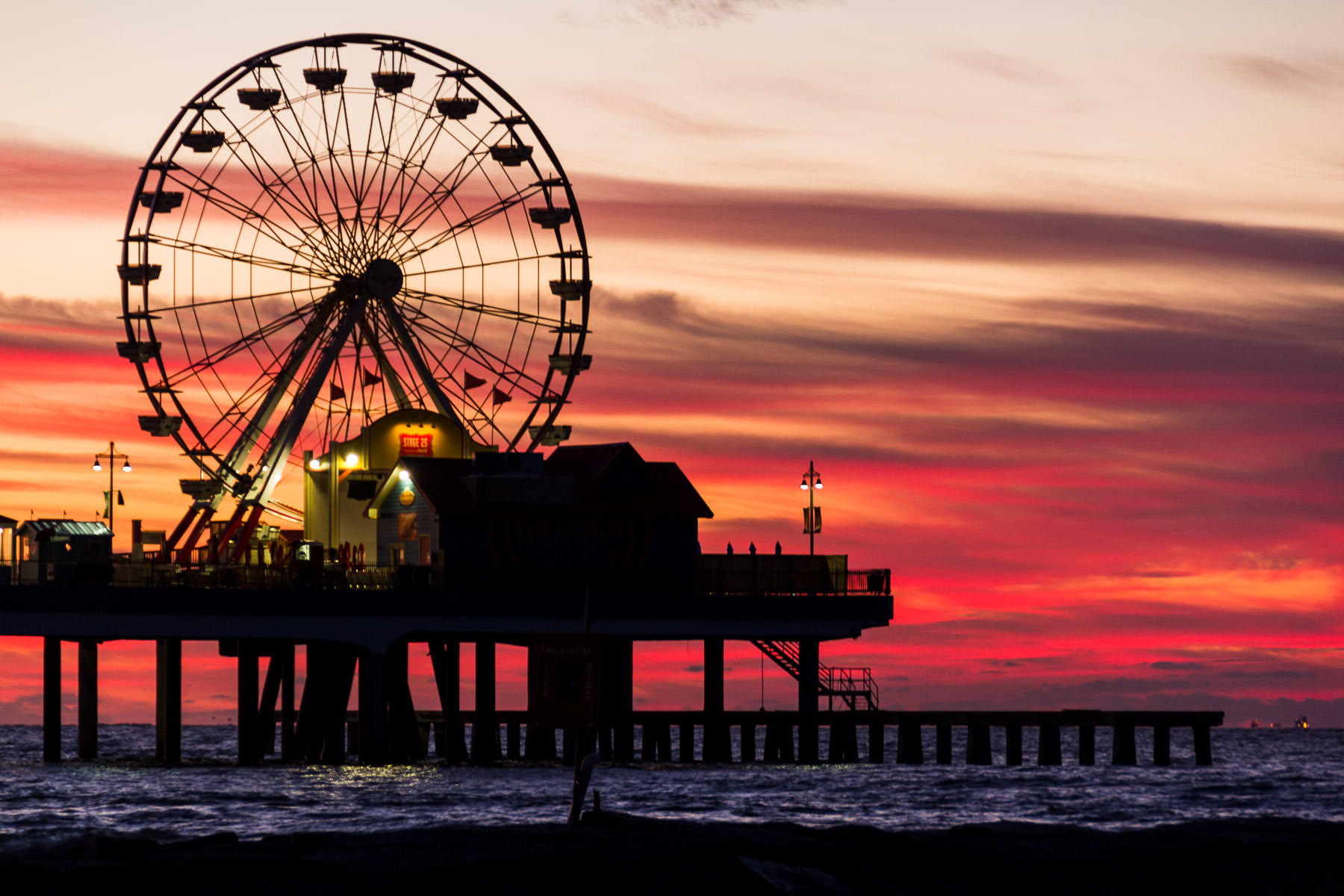 The light of the rising sun silhouettes the Historic Galveston Pleasure Pier as day breaks over the Gulf of Mexico.