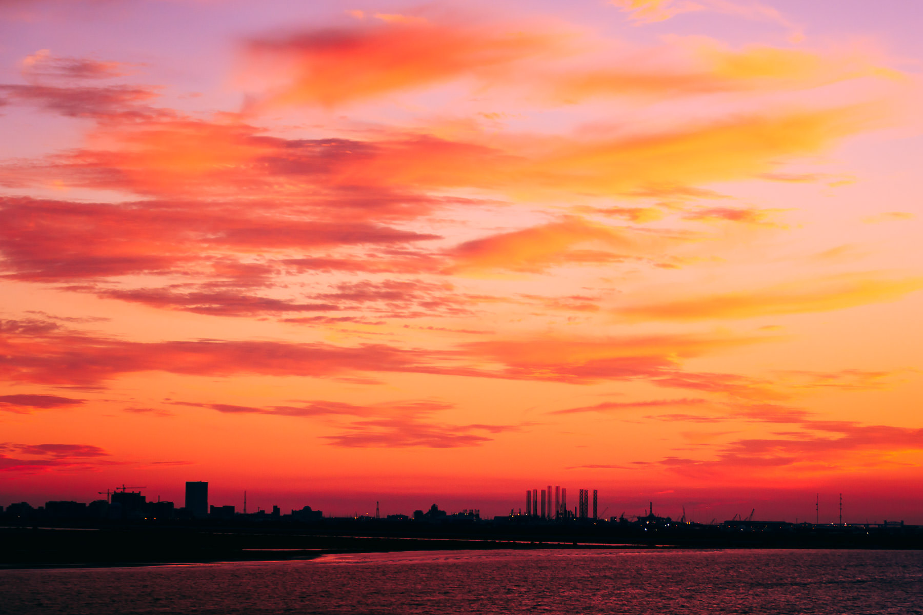 The skyline of Galveston, Texas, is silhouetted by the setting sun.