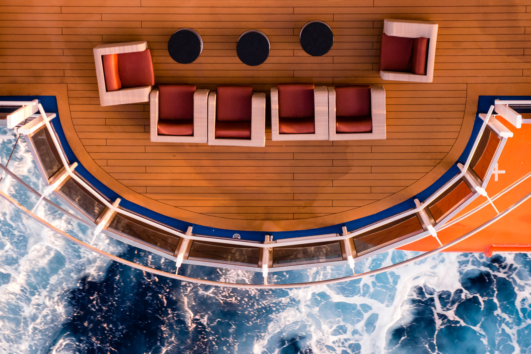 A seating area on the promenade deck of the cruise ship Carnival Magic juts out over the ocean.