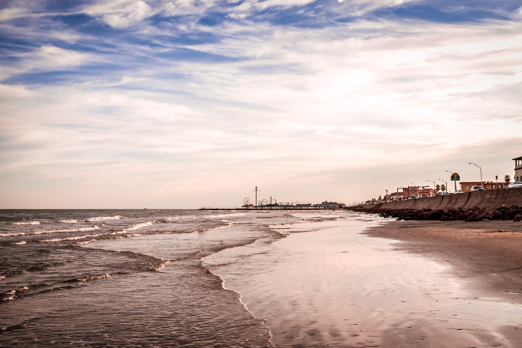Waves roll onto the beach as evening descends on Galveston, Texas.