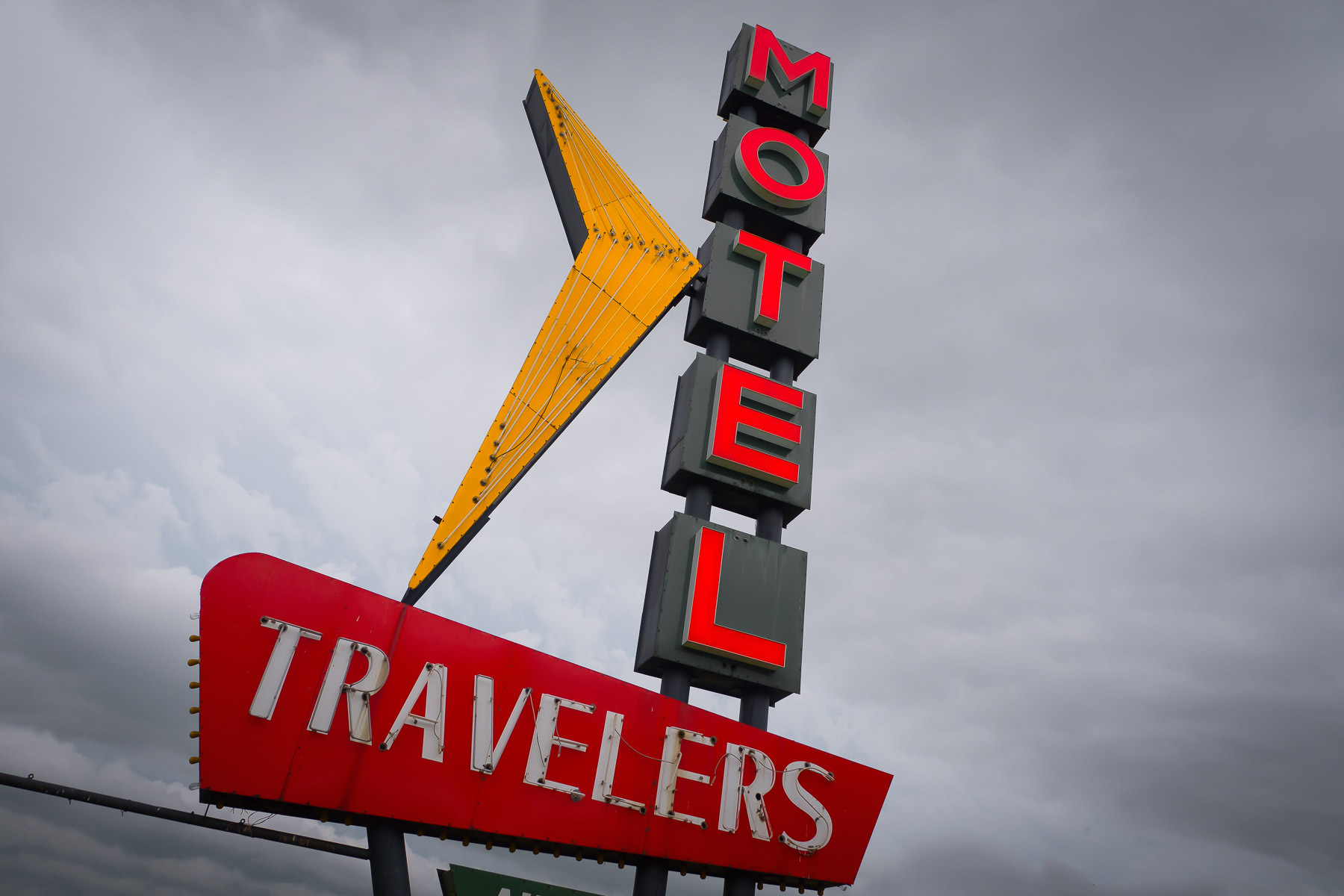 The Travelers Motel sign rises into the overcast sky over Bartlesville, Oklahoma.