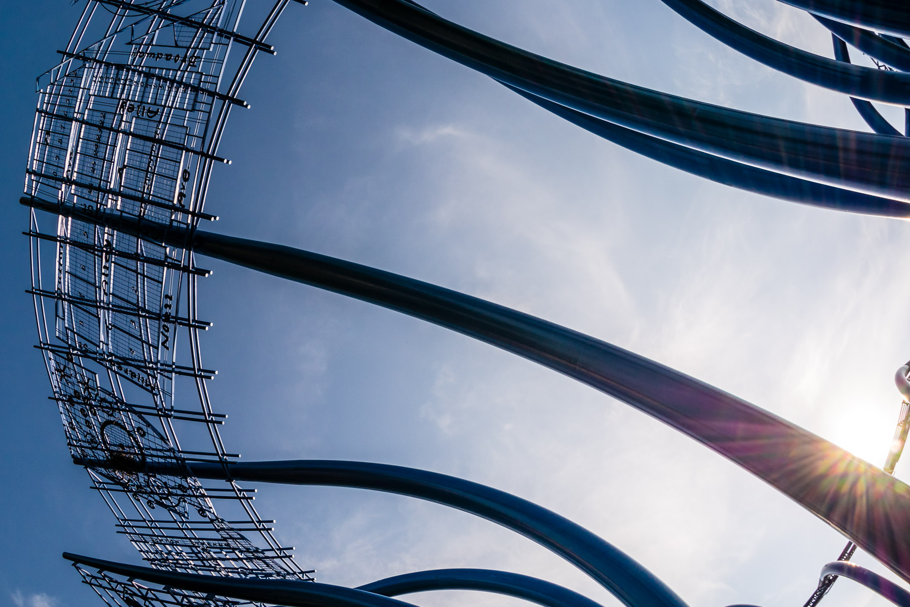 The sun peeks from behind the 45-foot-tall, 140-foot-wide Blueprints sculpture at Addison Circle in Addison, Texas.