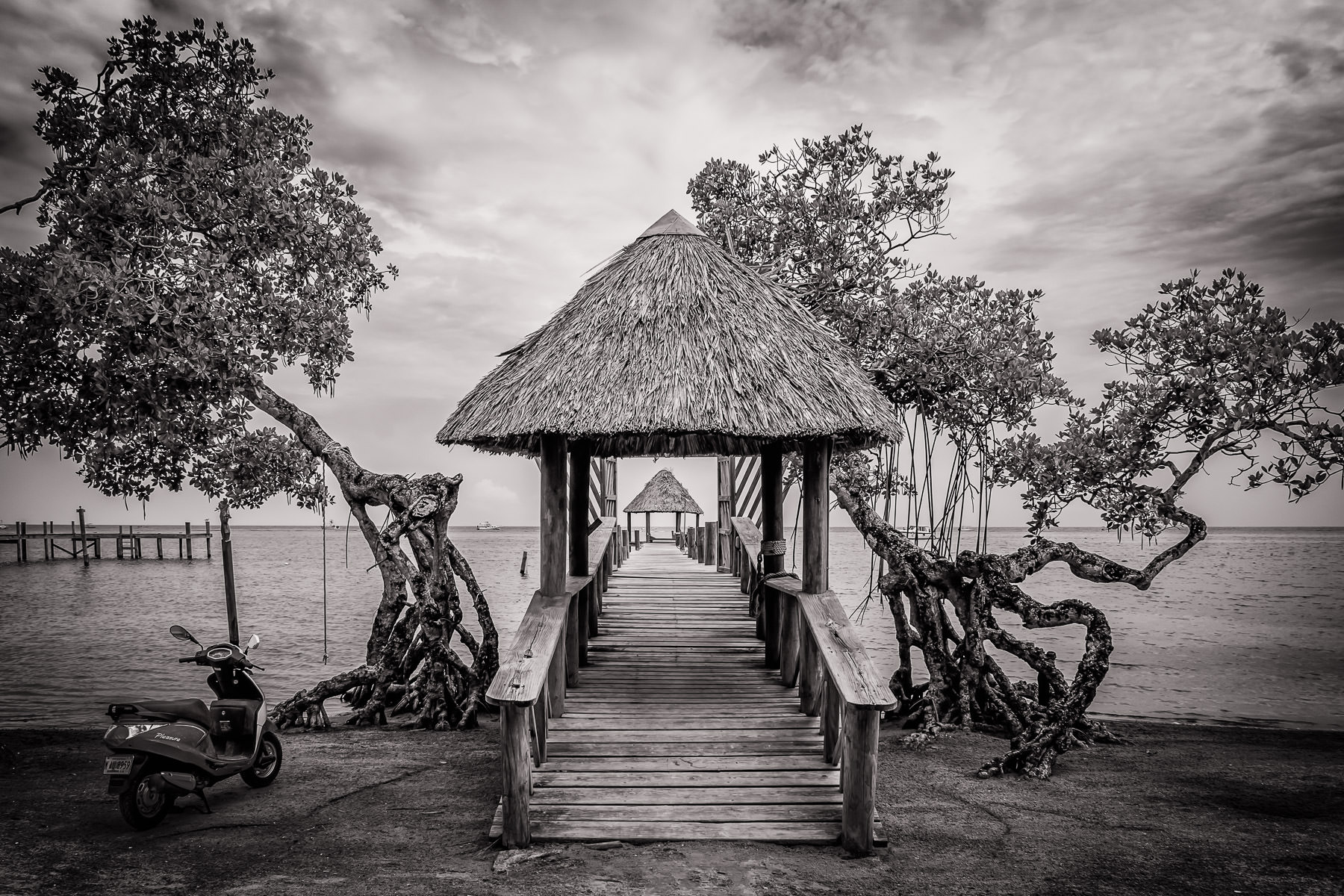 A scooter sits parked on the beach next to a pier on the island of Roatan, Honduras.