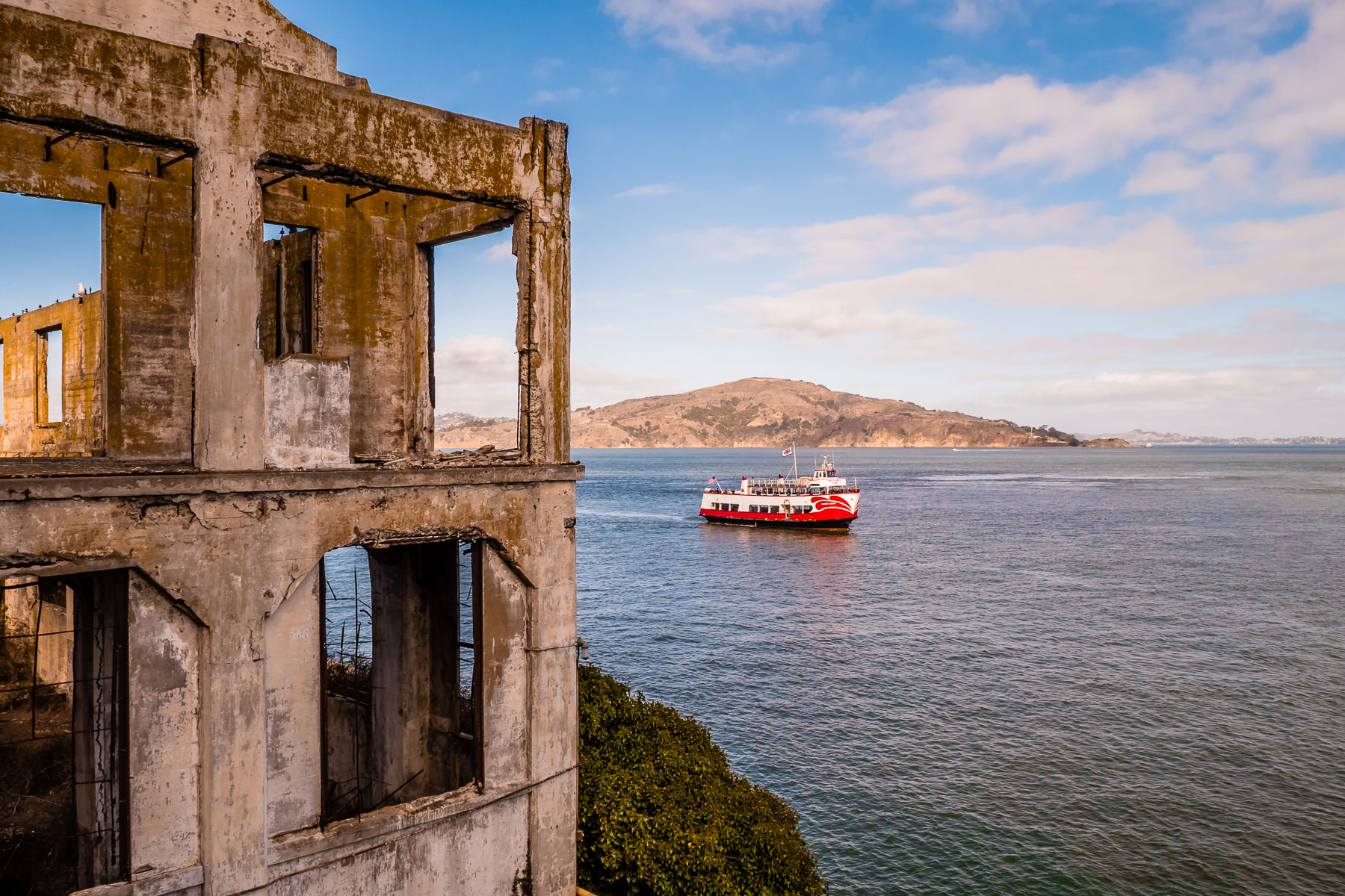 A tour boat sails past ruins at Alcatraz Federal Penitentiary in San Francisco Bay.