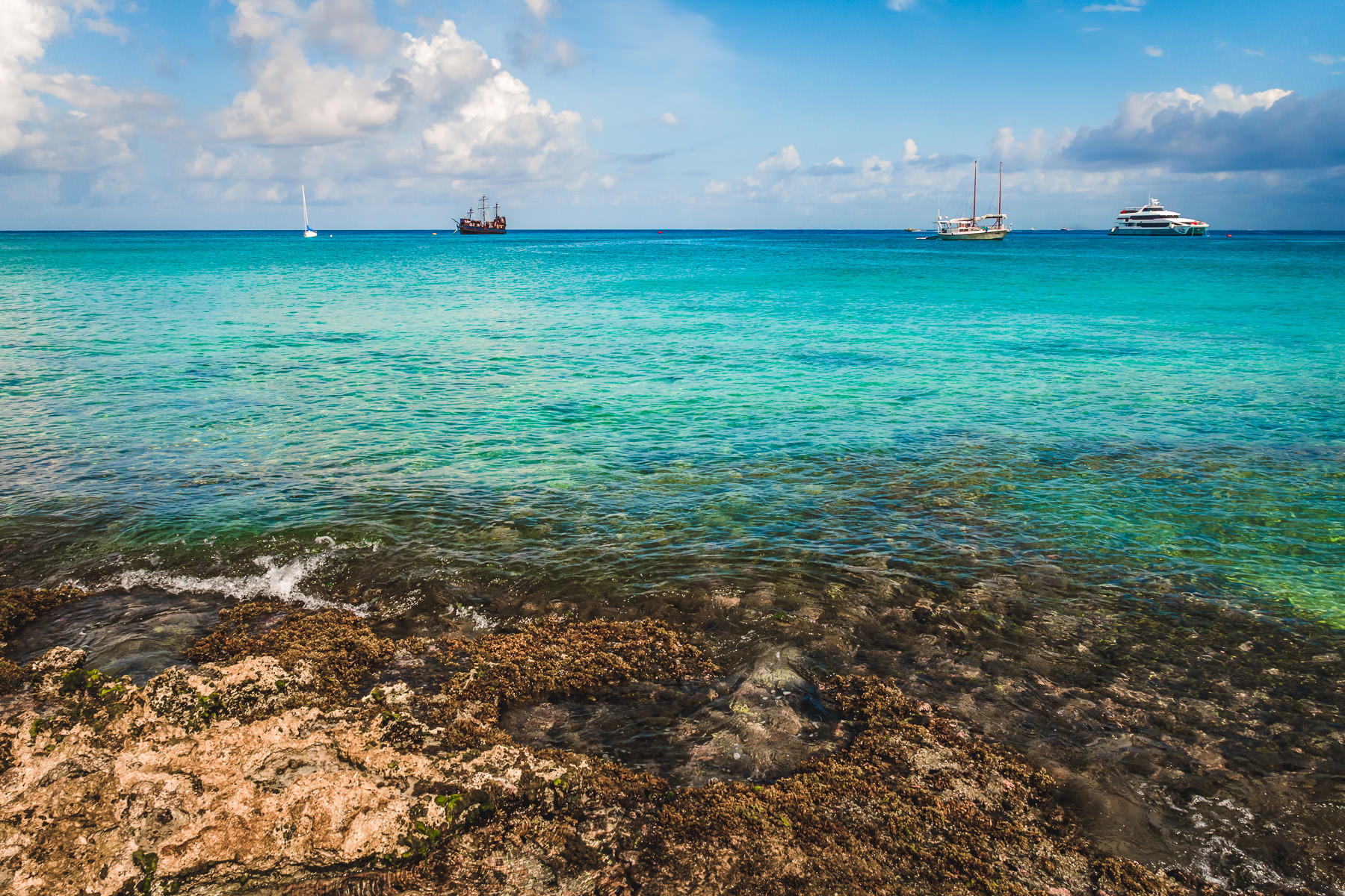 Boats float just off the rocky beach of Cozumel, Mexico.