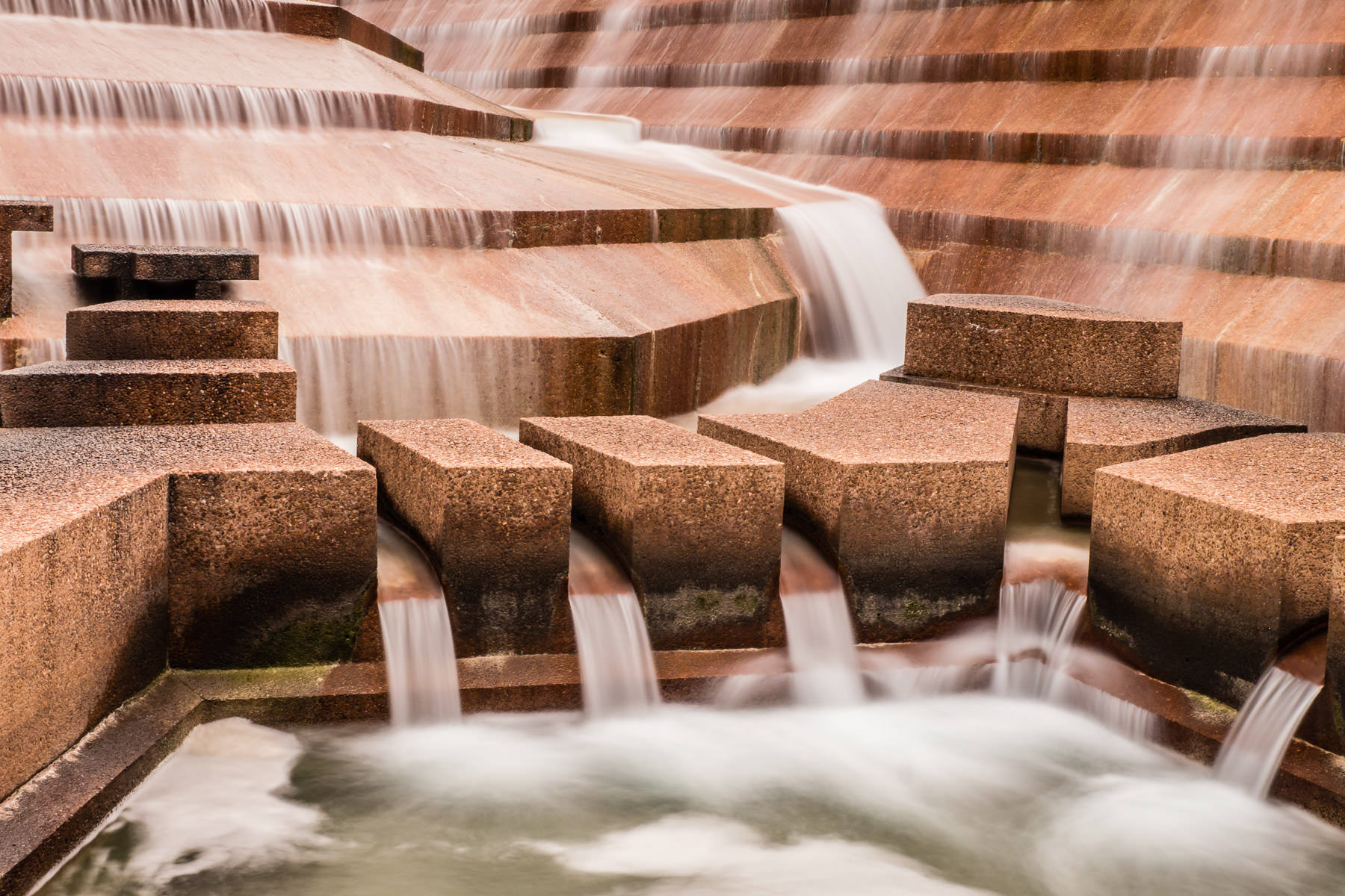 Water cascades over concrete aggregate blocks in the Active Pool at the Philip Johnson-designed Fort Worth Water Gardens in the south end of Downtown Fort Worth, Texas.