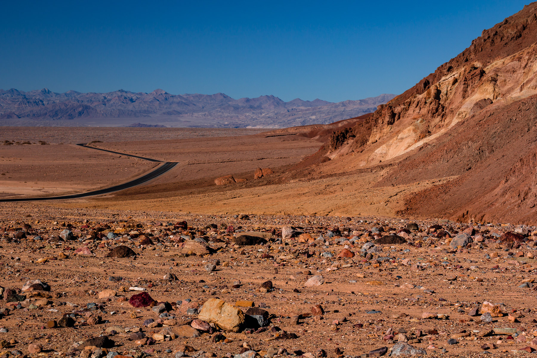 Multi-colored rocks lie on the arid desert ground at California's Death Valley National Park.