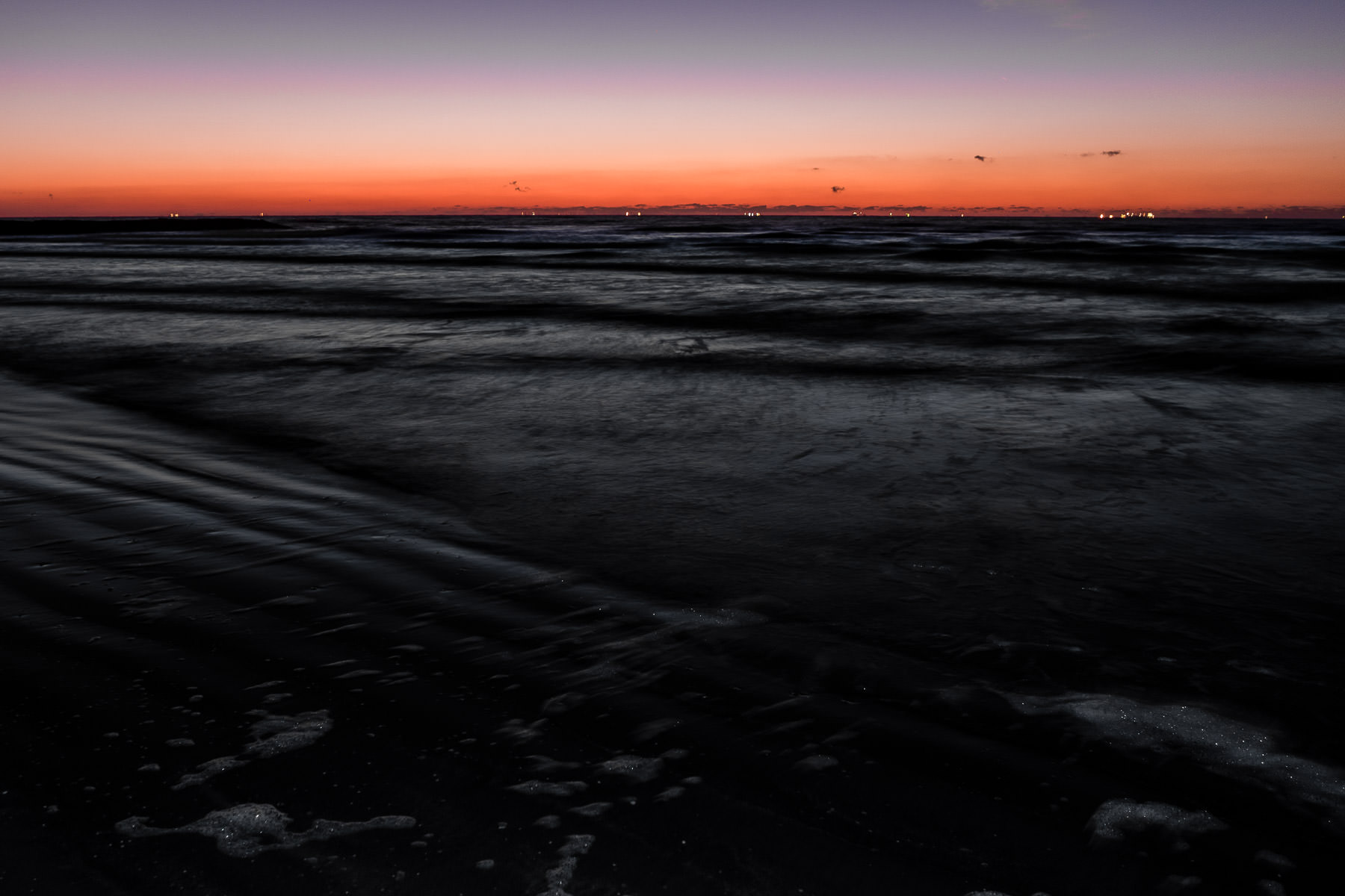 Ships' lights dot the horizon as the sun rises over the Gulf of Mexico as seen from a Galveston, Texas, beach.