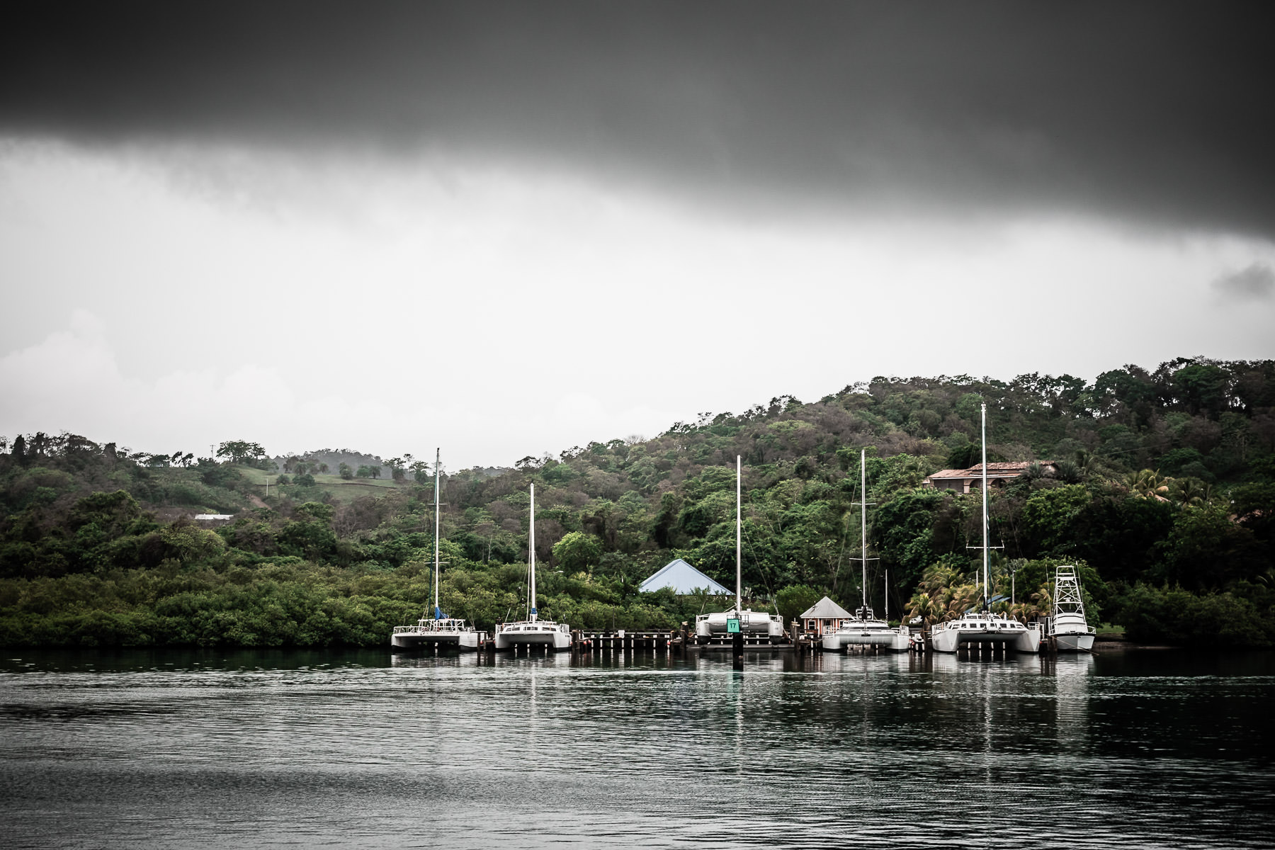 Sailboats docked at pier on the island of Roatán, Honduras, on a rainy, overcast day.