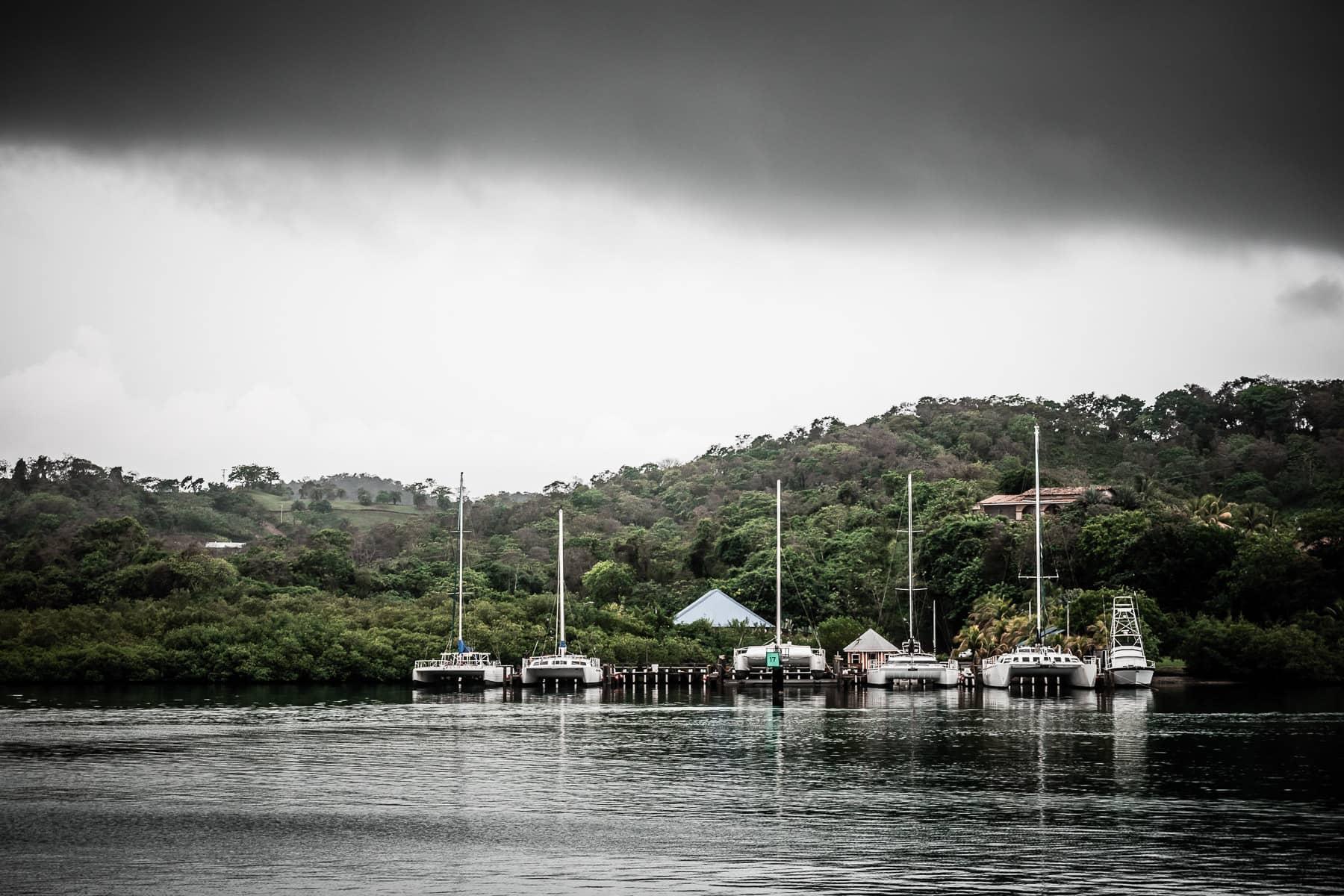Sailboats docked at pier on the island of Roatán, Honduras, on a rainy, overcast day.