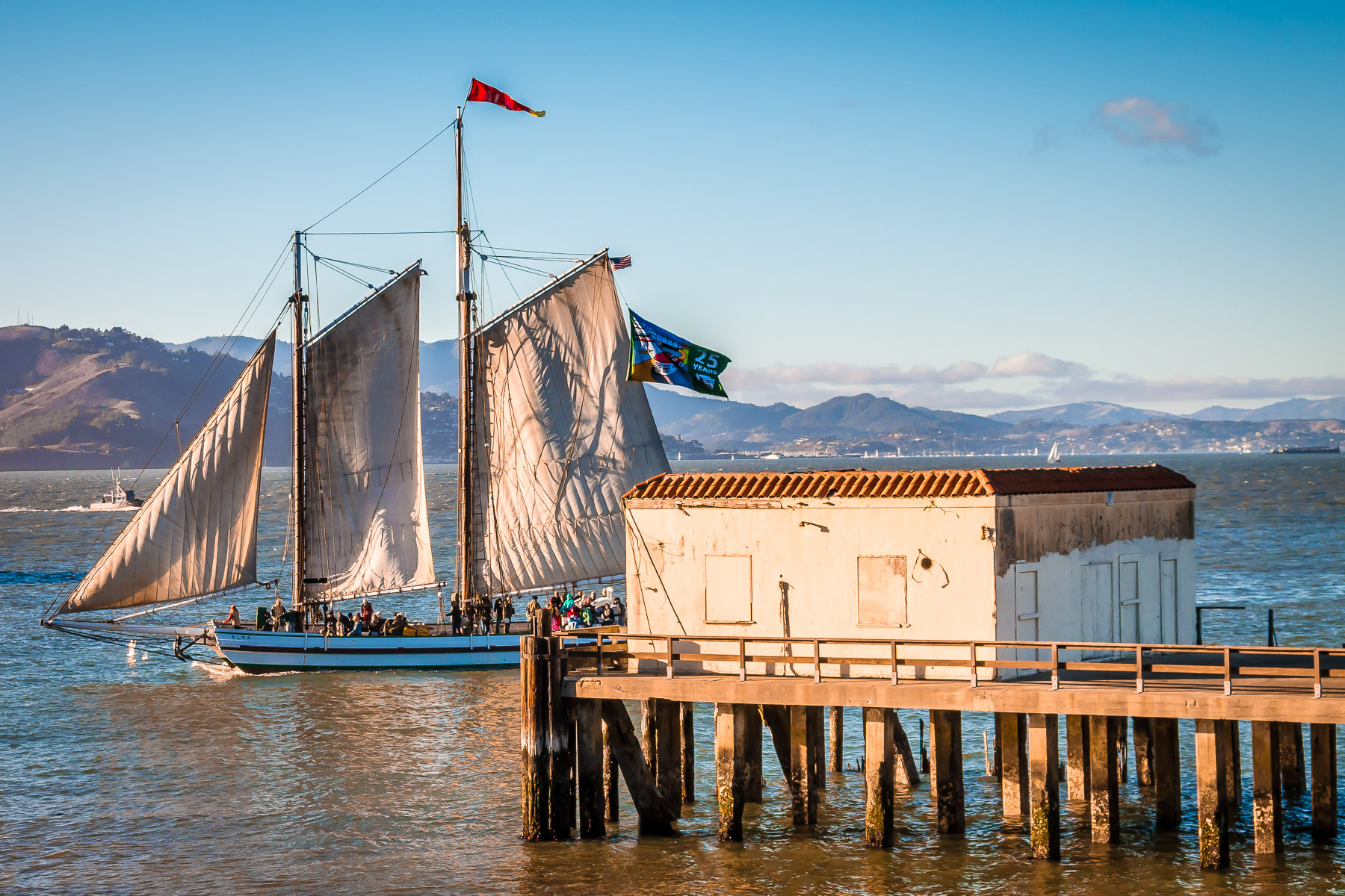 The 1891 scow schoonerAlma, in the collection of theSan FranciscoMaritime National Historical Park, sails past a pier in San Francisco Bay.