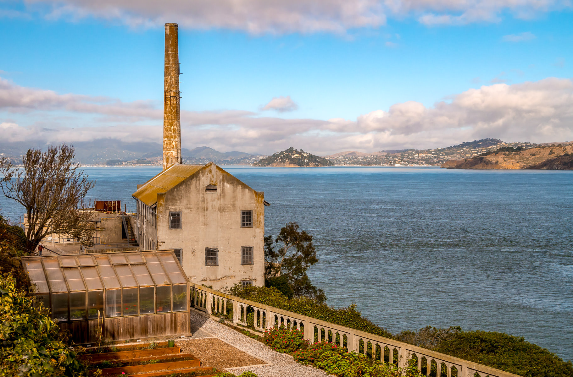 The smoke stack of the power house at Alcatraz Federal Penitentiary rises into the sky over San Francisco Bay.