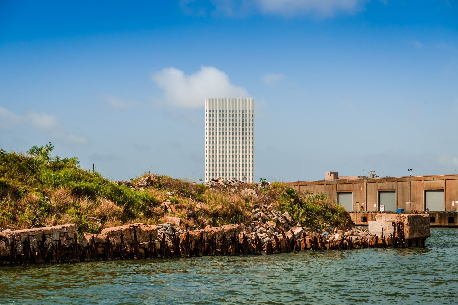 Galveston, Texas' 23-story One Moody Plaza rises into the sky over rubble used as infill on the city's waterfront.