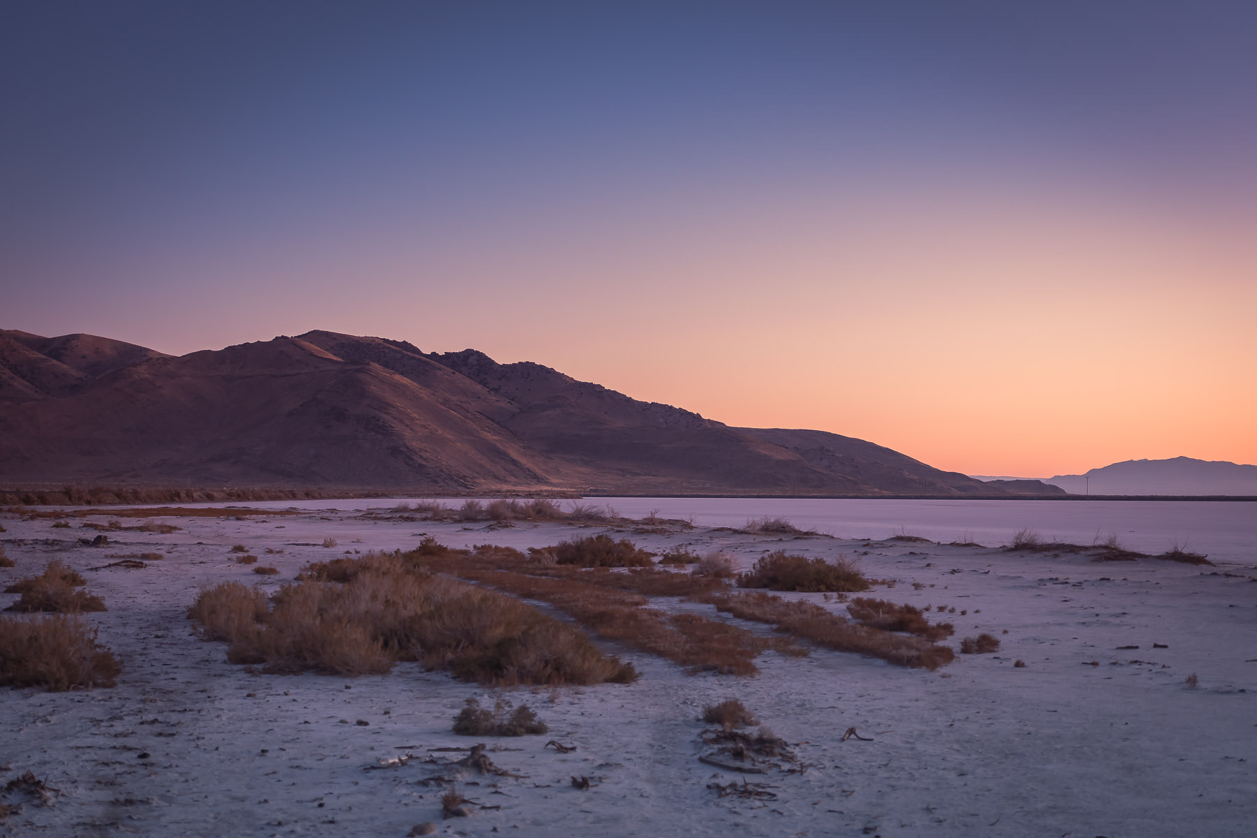 The sun rises on the mountainous Stansbury Island and the shoreline of the Great Salt Lake, Utah.