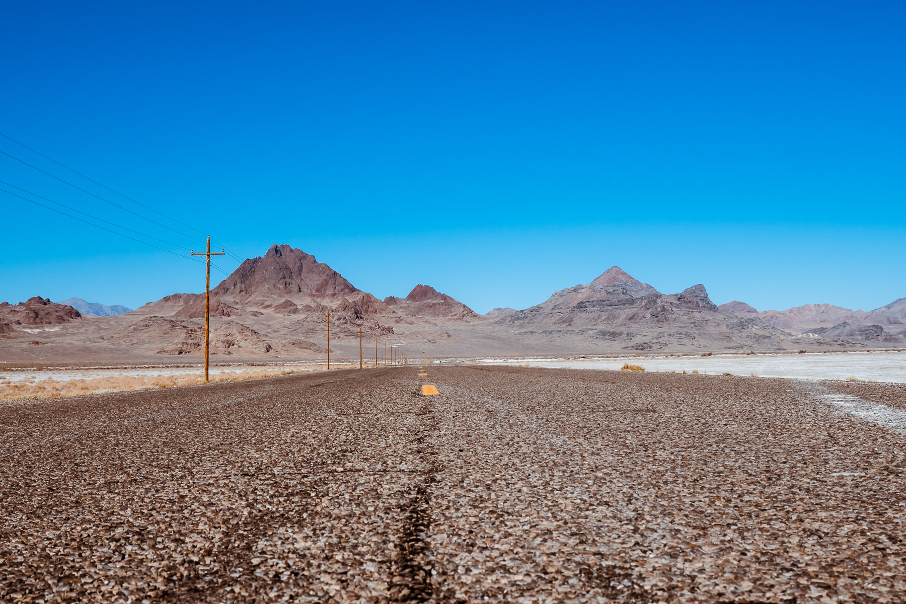 A road leads towards the mountains along the Utah/Nevada border at the Bonneville Salt Flats.