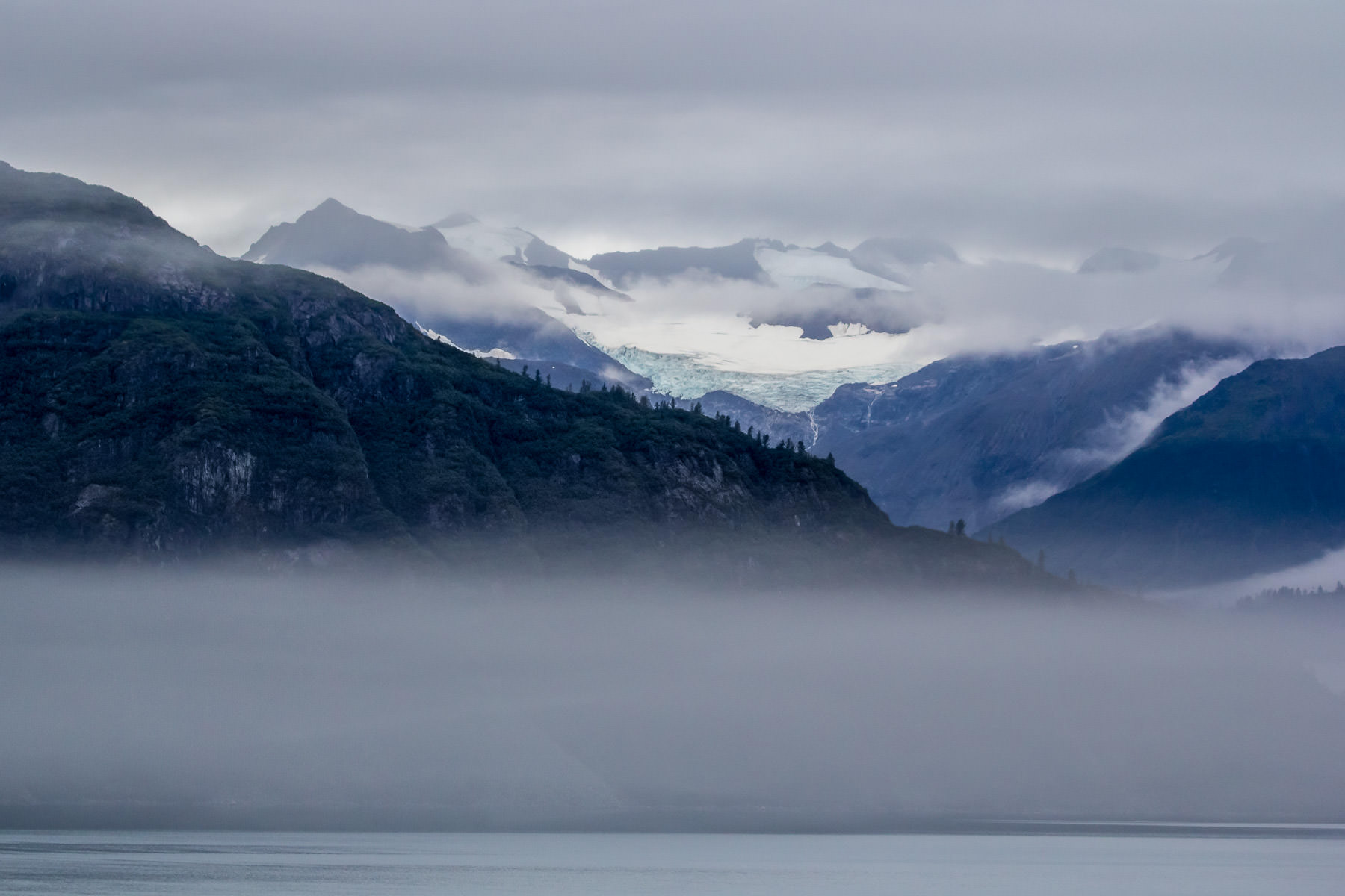 Fog envelops the rugged, mountainous shoreline of Alaska's Glacier Bay.