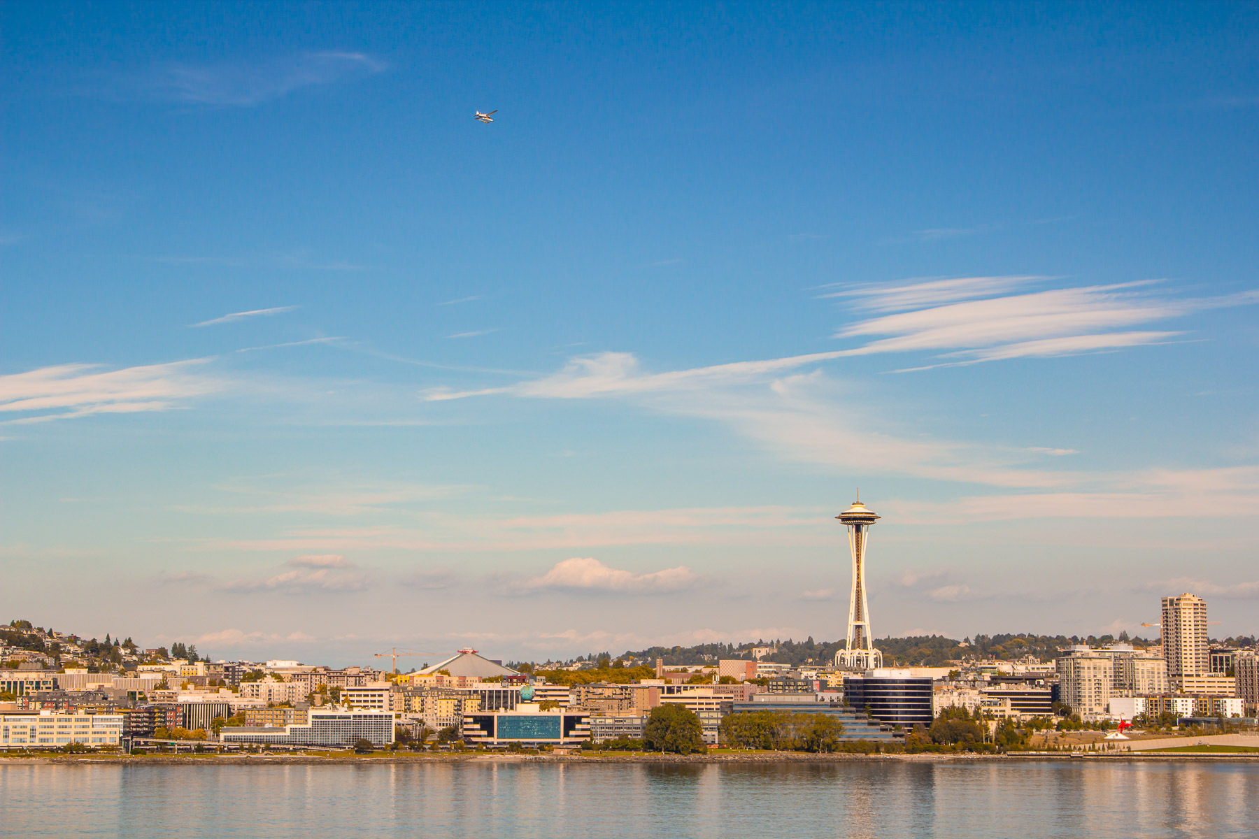 A seaplane flies over the Space Needle and its surrounding environs, Seattle, Washington.