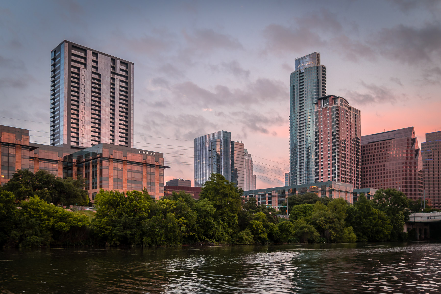 The setting sun illuminates buildings along the shoreline of Austin, Texas' Lady Bird Lake.