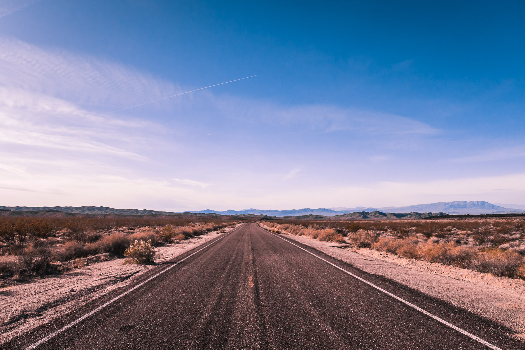 A lonely blacktop road stretches to the mountains in the distance at the Mojave National Preserve, California.