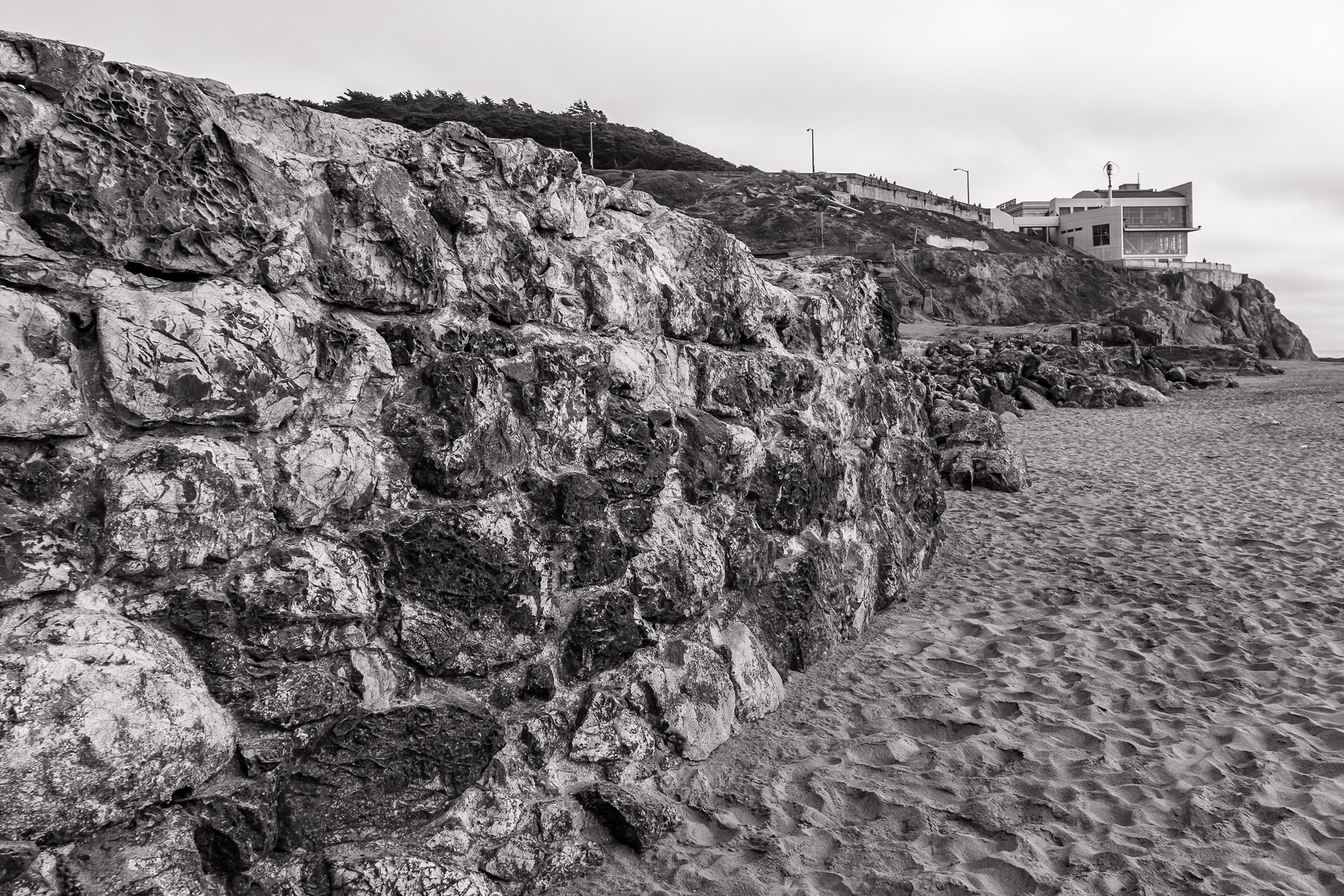 A rock wall—part of the ruins of the Sutro Baths—leads towards the modern wing of the historic Cliff House restaurant on the beach at Lands End, San Francisco.