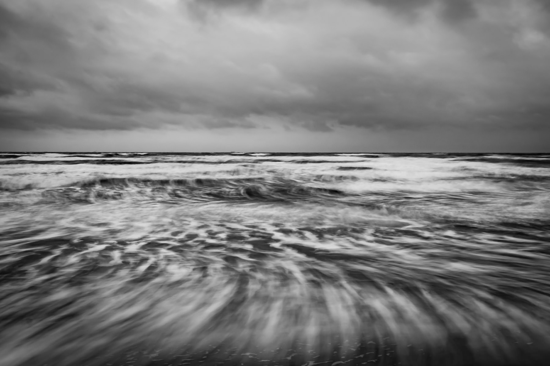 A long-exposure photo smooths the dynamic Gulf of Mexico along the Galveston, Texas, beach.