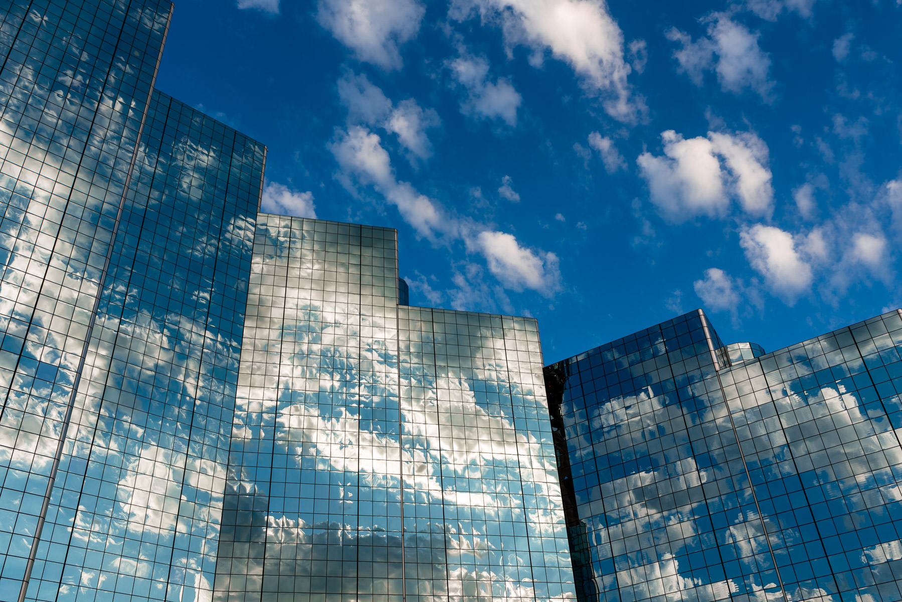 The cloudy North Texas sky is reflected in the mirrored facade of the Hyatt Regency in Downtown Dallas.