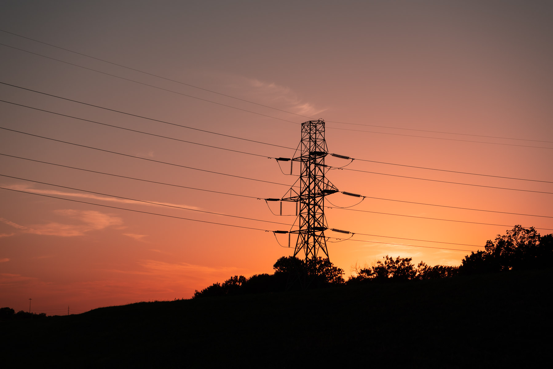The sun sets on a electric pylon in Irving, Texas.