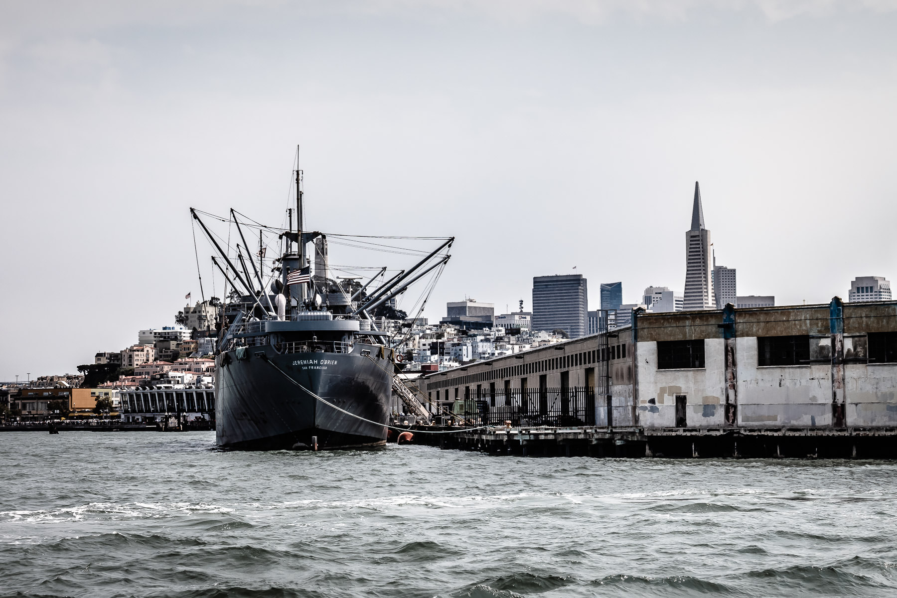 The SS Jeremiah O'Brien—one of only two surviving operational Liberty ships from World War II—docked at San Francisco's Pier 45 with the city as its backdrop.