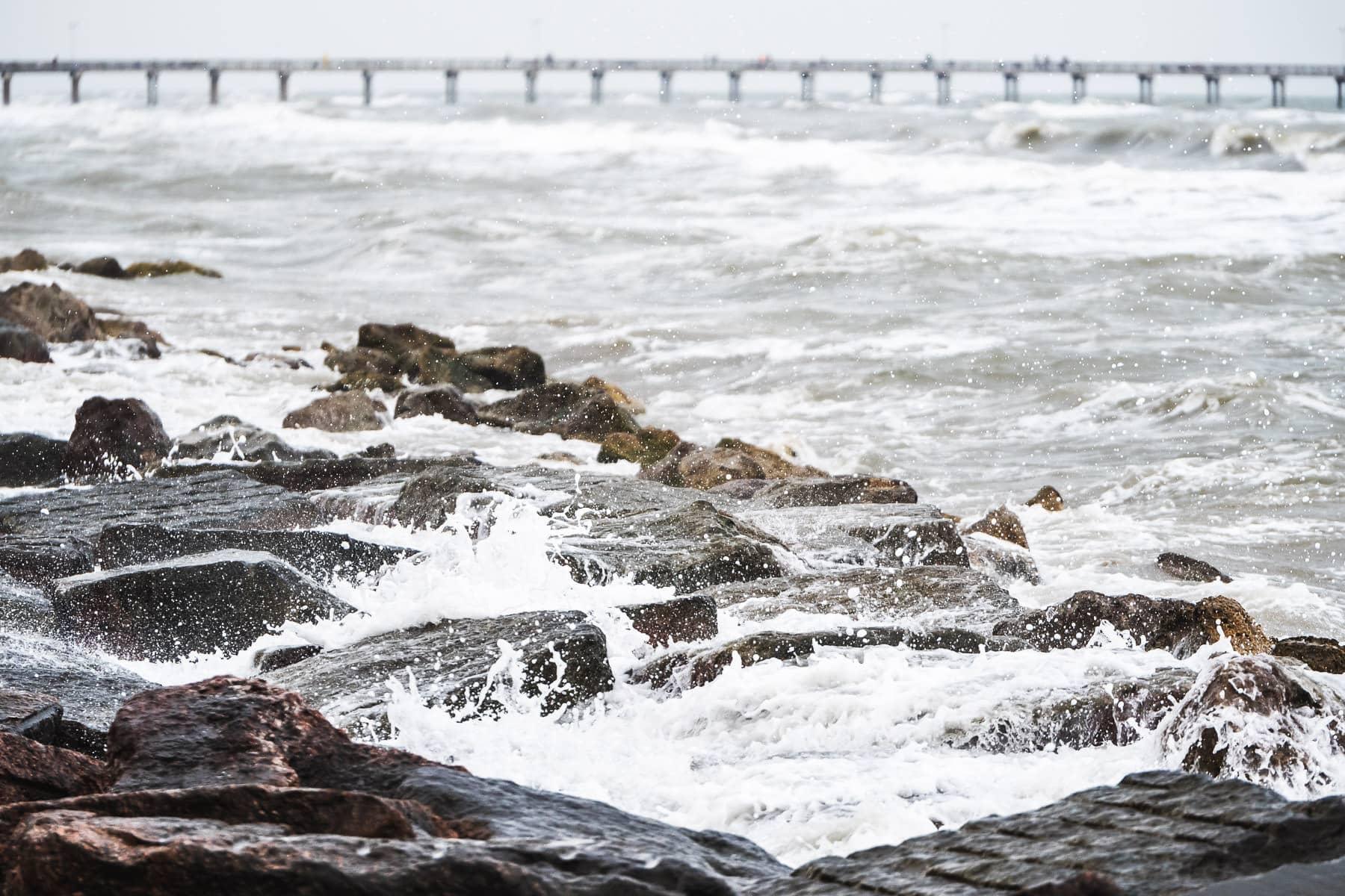 Surf crashes onto granite blocks along the seawall in Galveston, Texas.