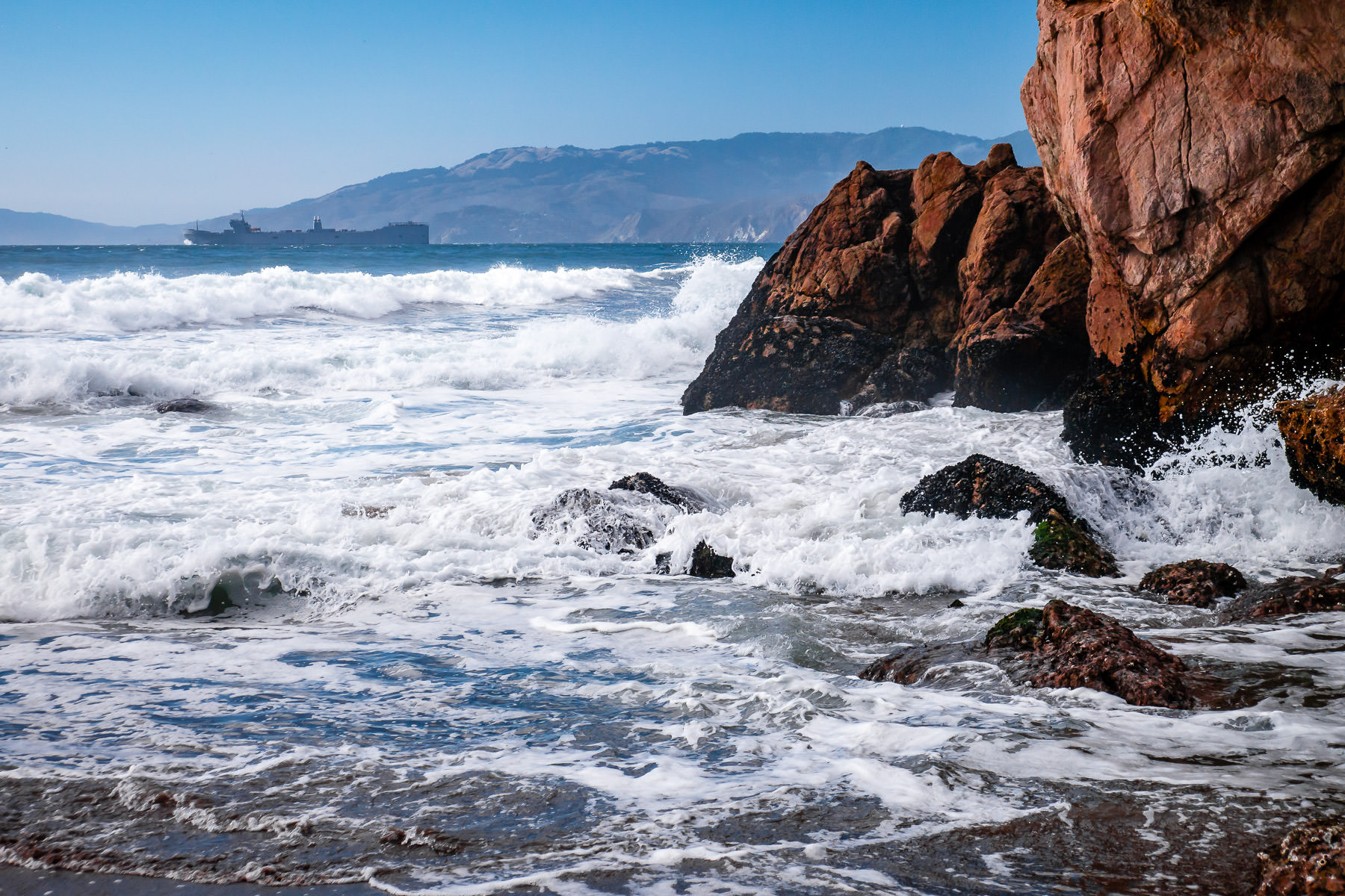 A ship sails towards San Francisco Bay, past the rocky shore at Lands End.