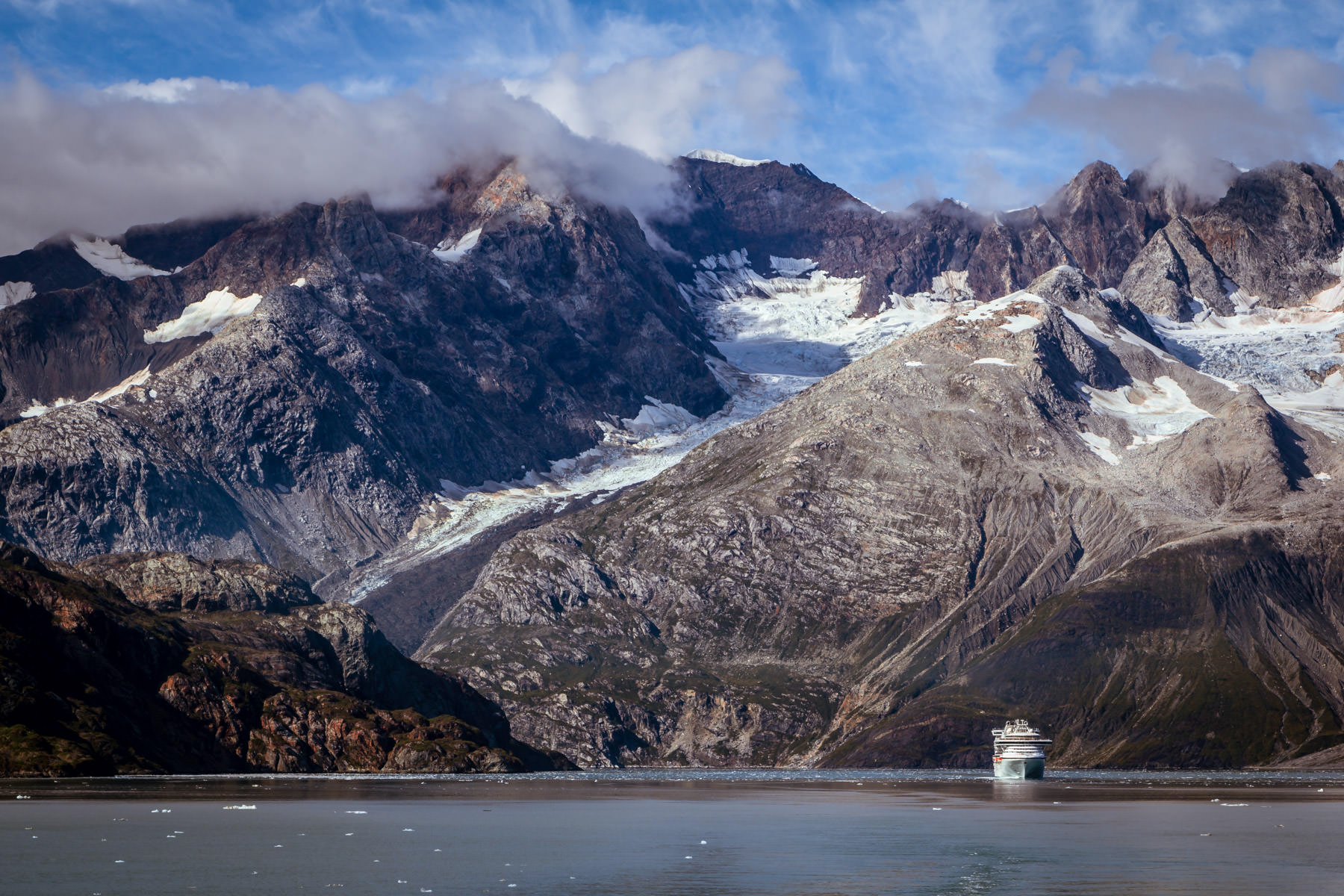 The cruise ship Sapphire Princess is dwarfed by the mountainous landscape of Alaska's Glacier Bay.