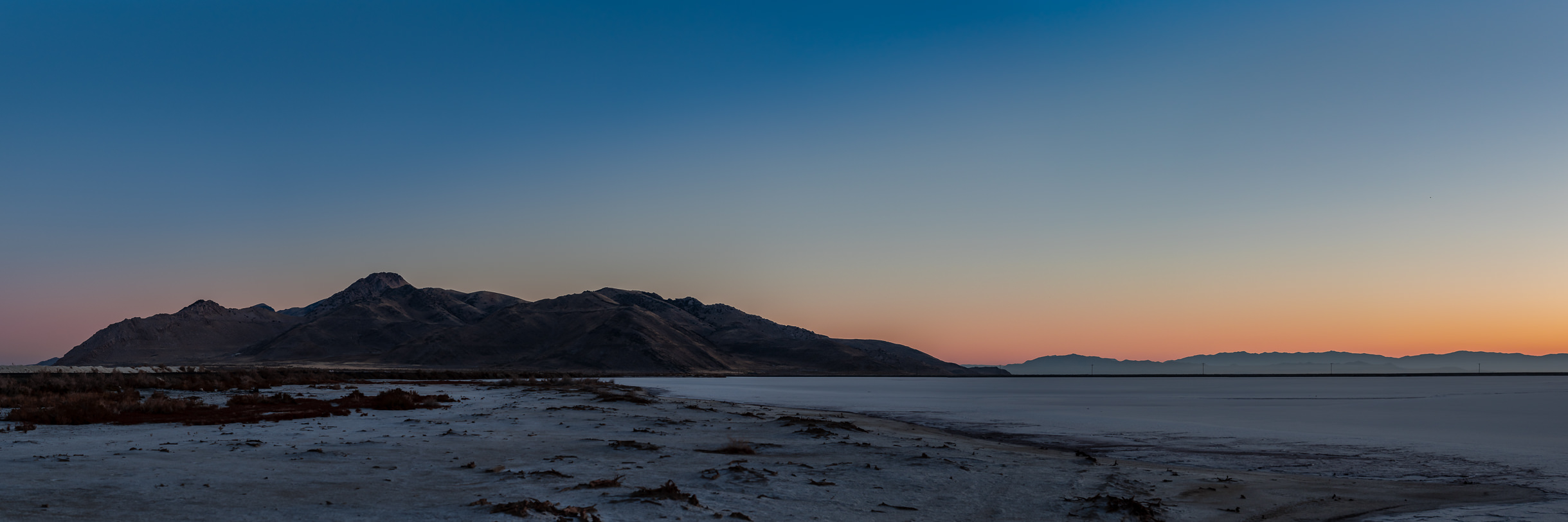 The sun begins to rise on Utah's Stansbury Island along the shore of the Great Salt Lake.