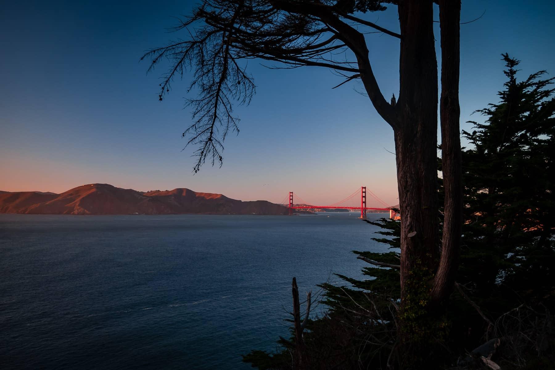 The last light of day illuminates San Francisco's Golden Gate Bridge.