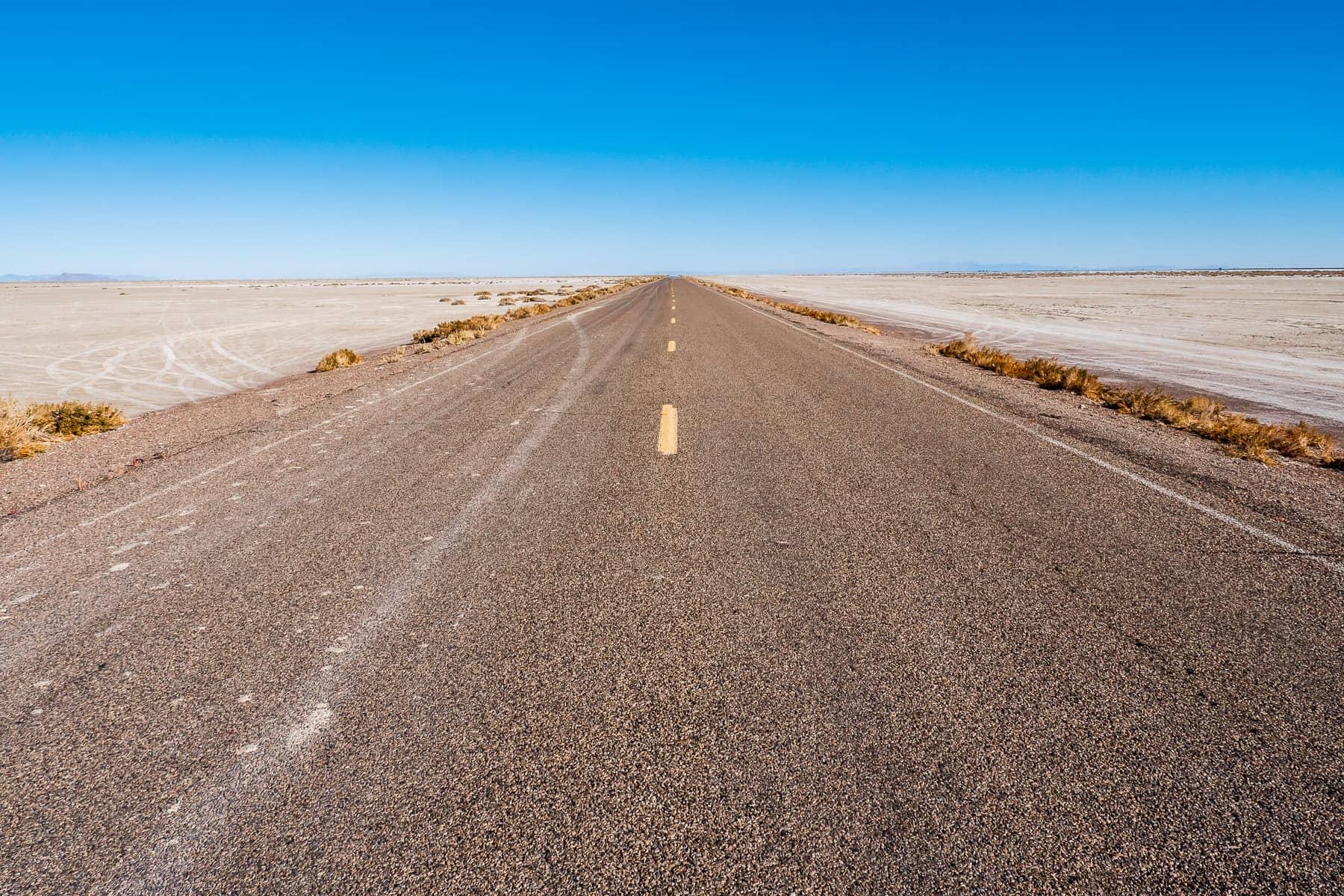 A road stretches across the arid expanse of Utah's Bonneville Salt Flats.