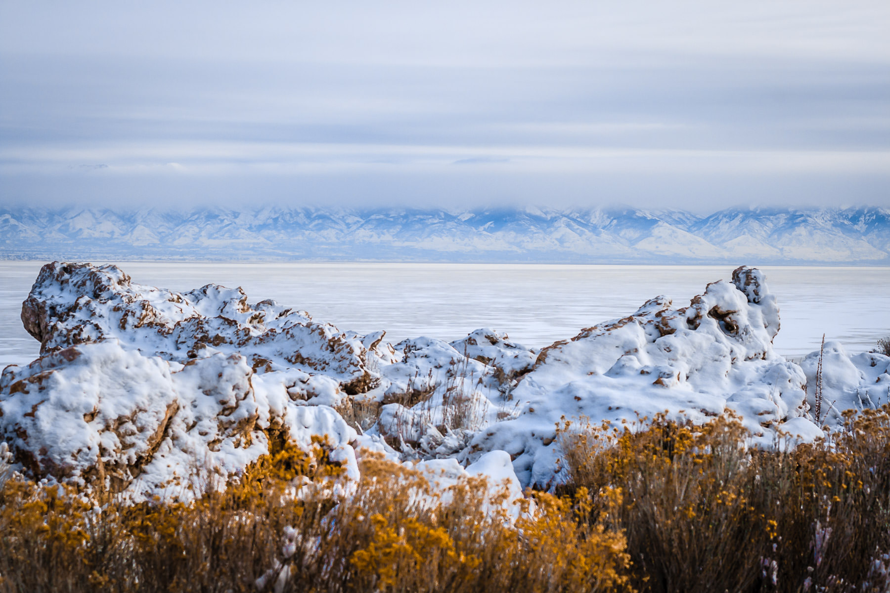Distant winter mountains line the horizon as seen from the Great Salt Lake's Antelope Island, Utah.