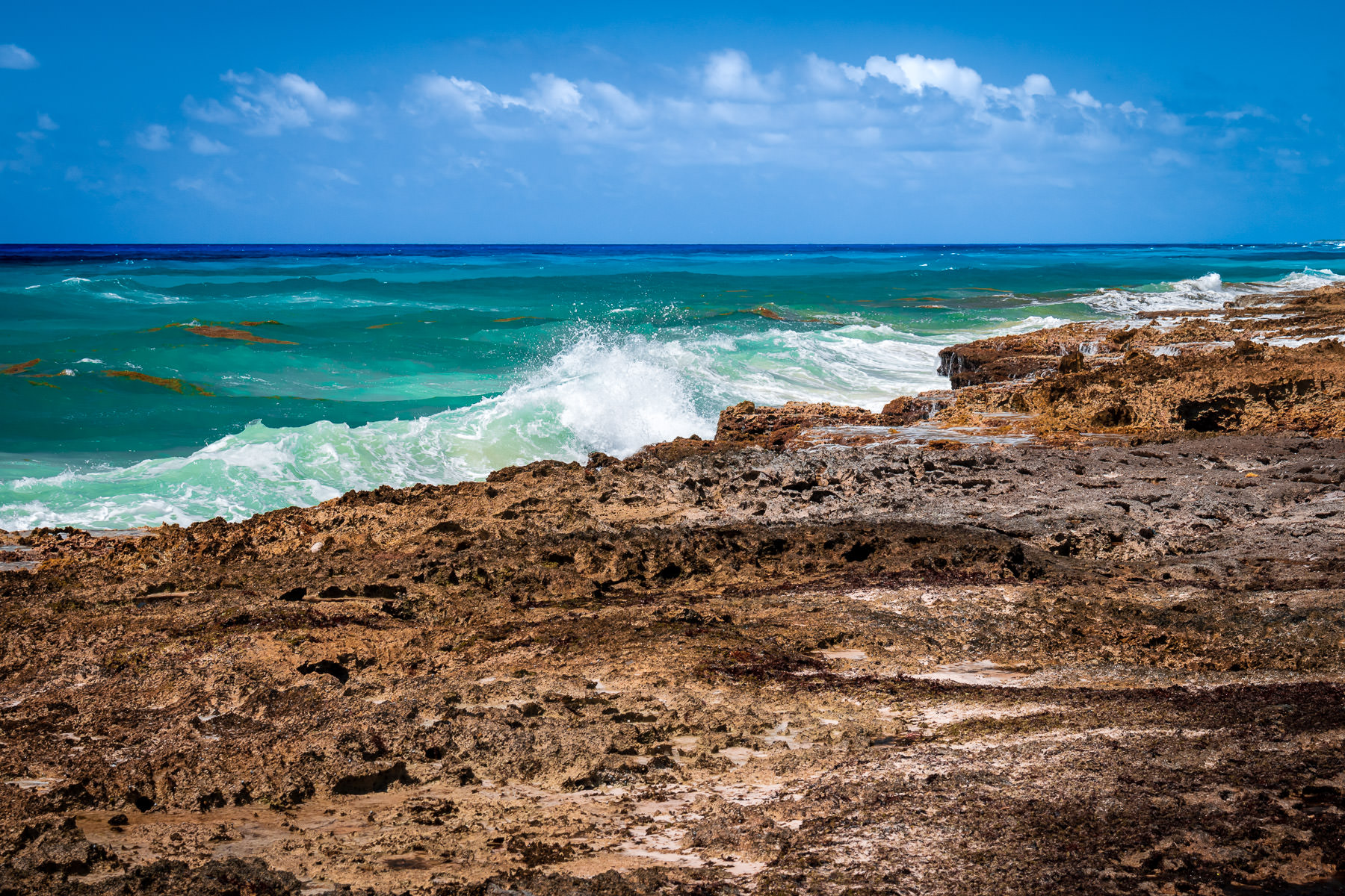 Waves crash onto the rough, rocky shore of the east side of Cozumel, Mexico.