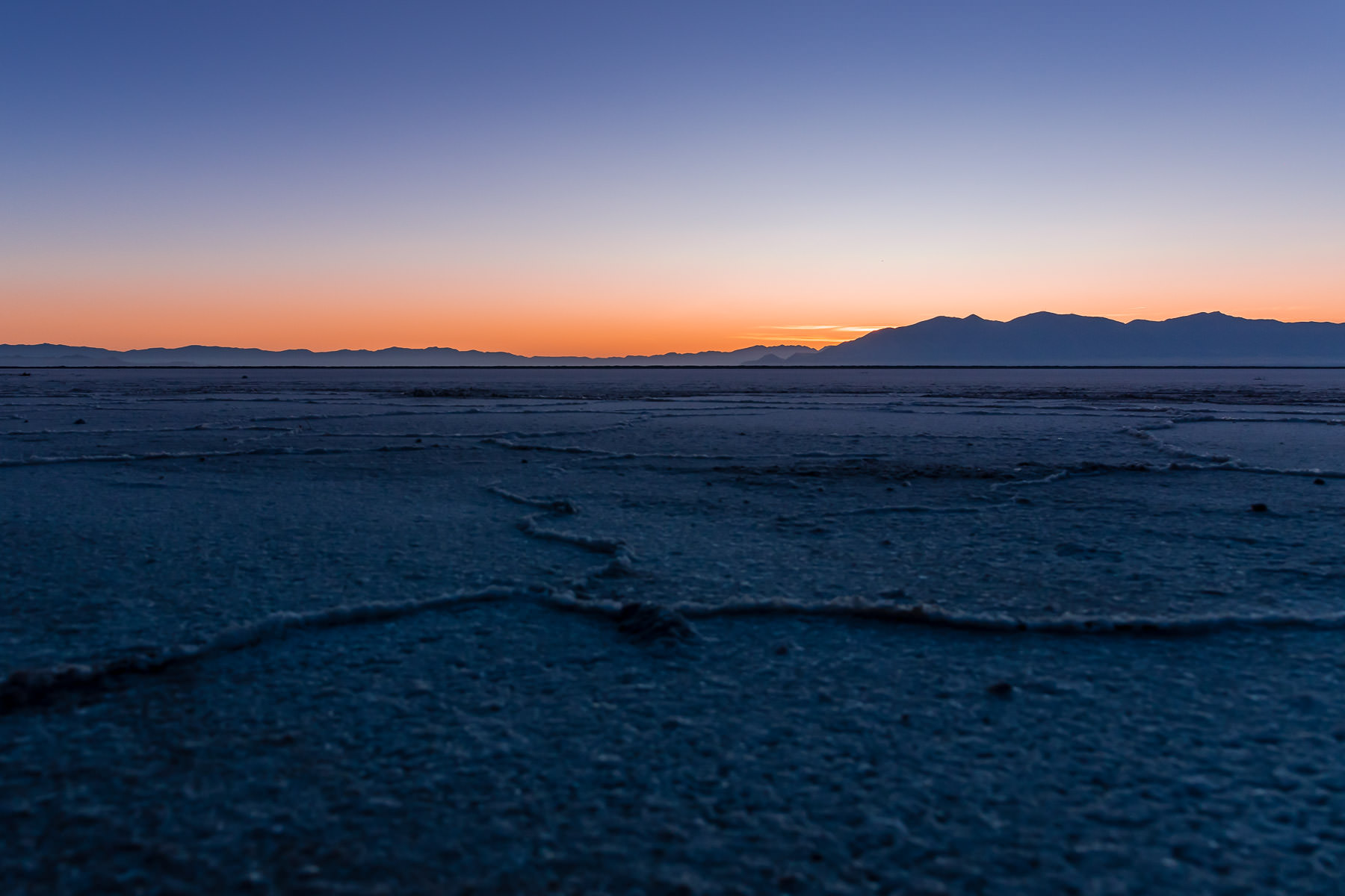 Salt flats along the shore of Utah's Great Salt Lake near Stansbury Island stretch towards the rising sun.