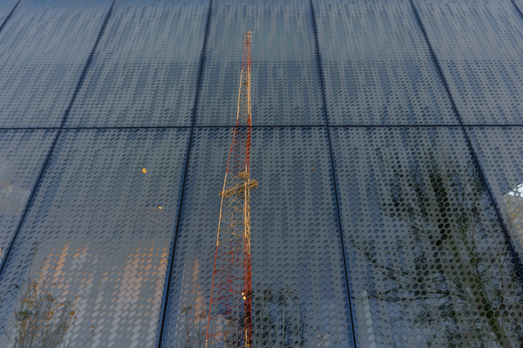A nearby broadcast tower is reflected in the glass exterior of San Antonio's Tobin Center for the Performing Arts.