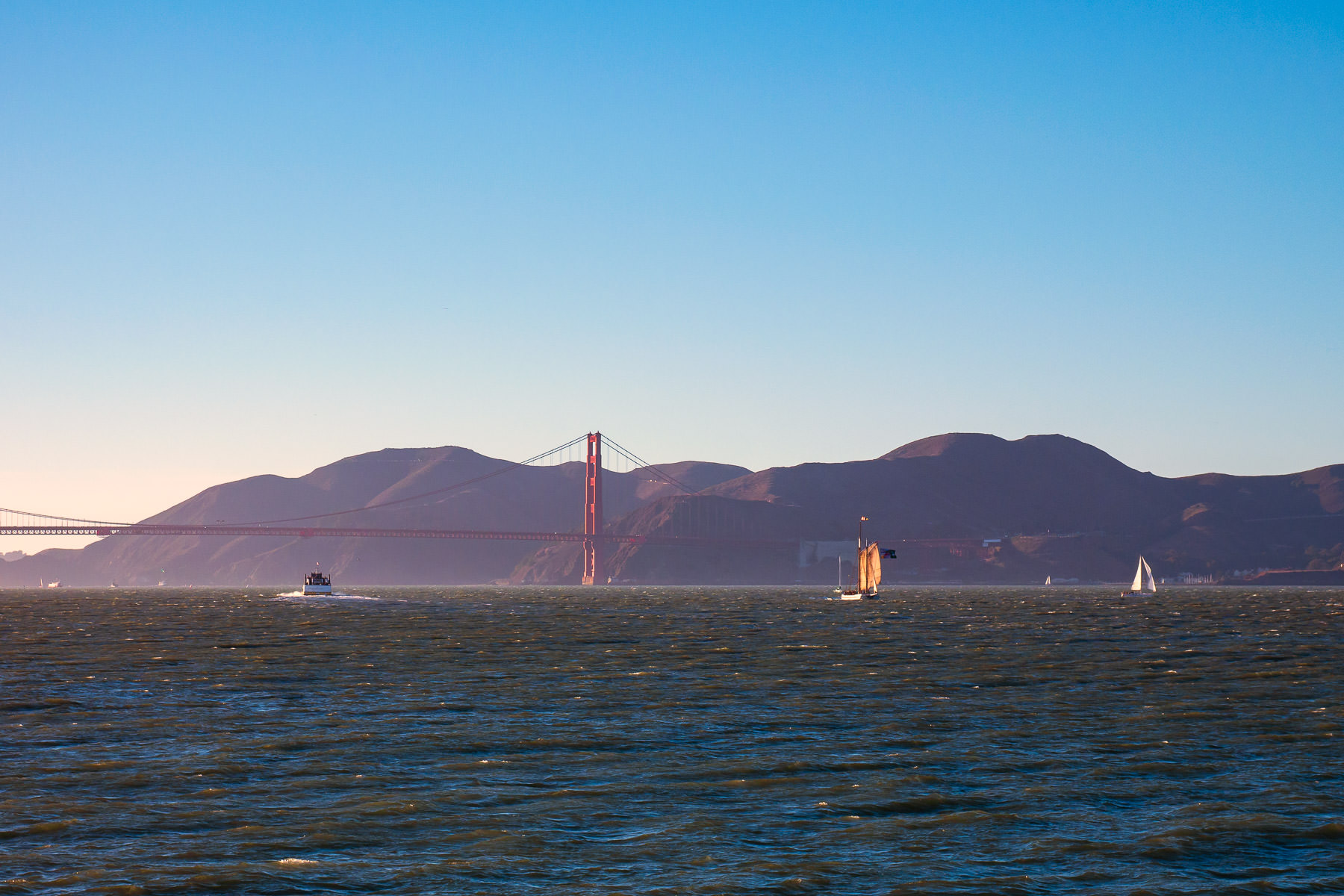 The sun begins to set on San Francisco Bay and the Golden Gate Bridge.