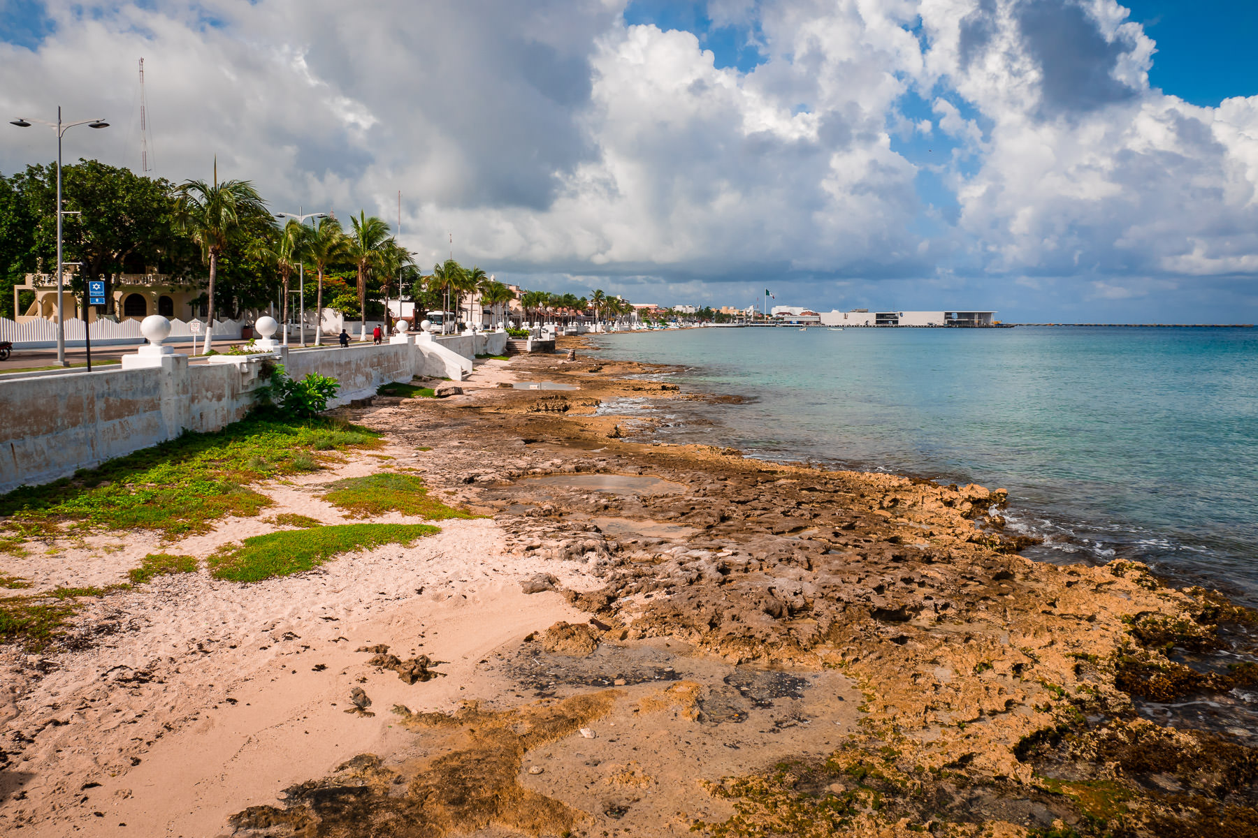 The sea lazily laps at the rocky shore along the Malecón in San Miguel, Cozumel, Mexico.