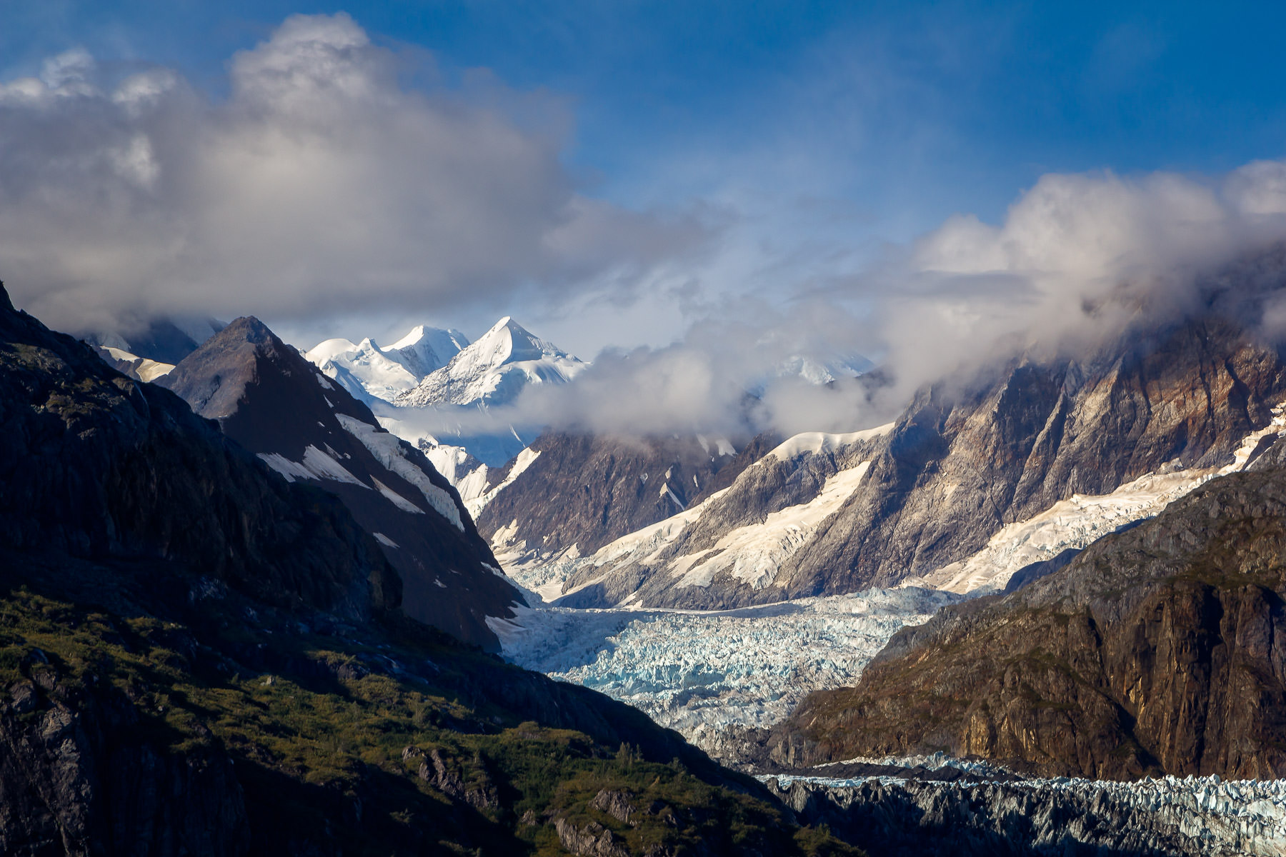 Mountains reach into the cloudy sky at Alaska's Glacier Bay National Park.