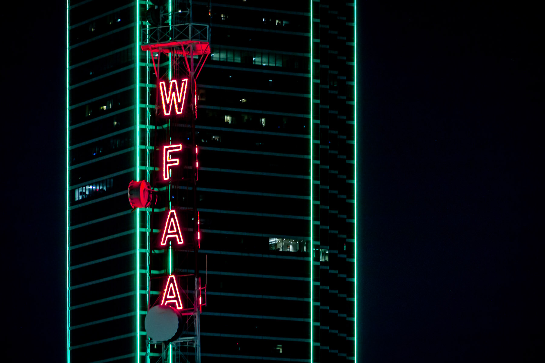 A broadcast tower at WFAA glows in Dallas' night sky near Bank of America Plaza.