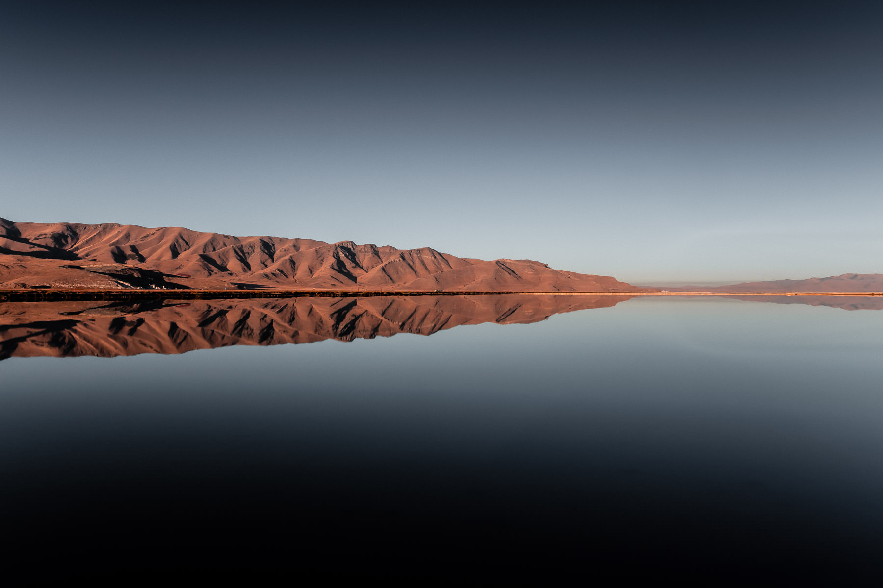 The Stansbury Mountains are reflected in the smooth waters of a retaining pond near Stansbury Island, Utah.