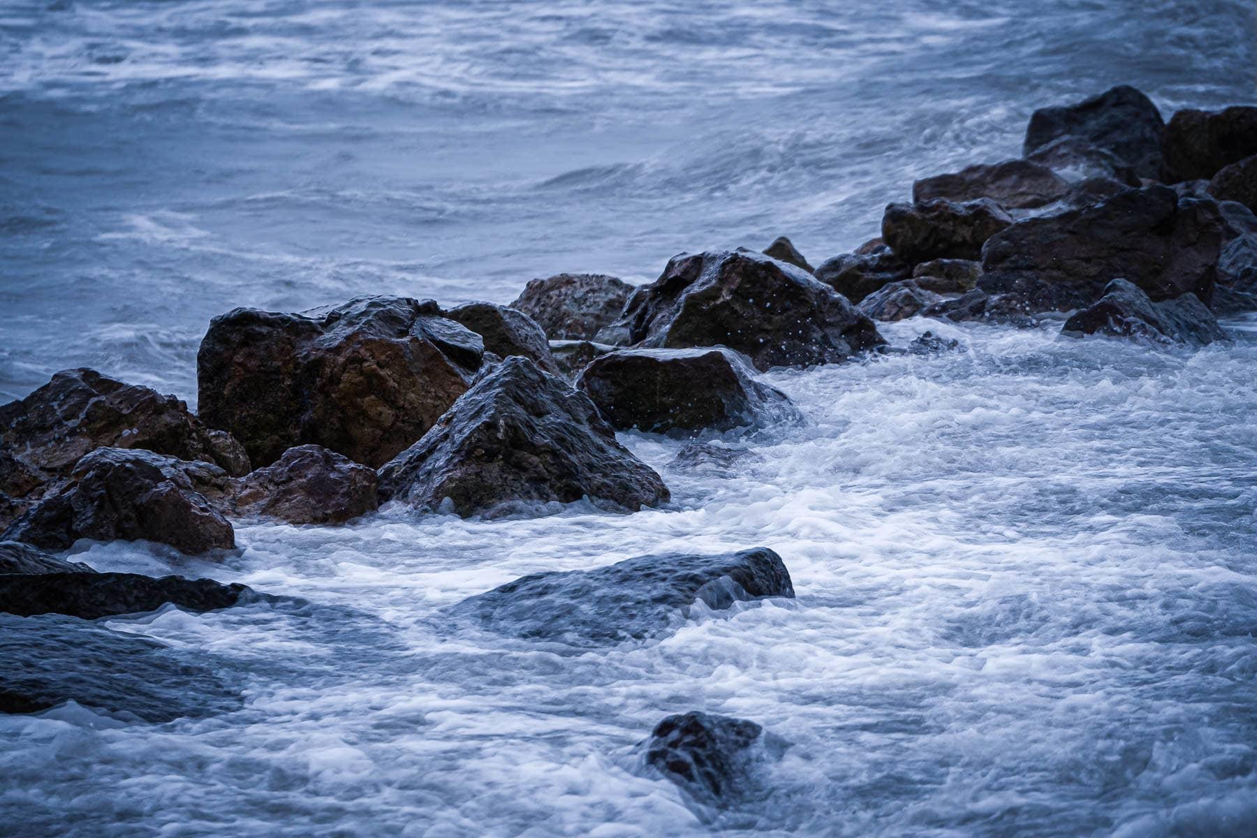 Gulf of Mexico waves splash over granite blocks acting as breakwaters along the Galveston, Texas, beach.