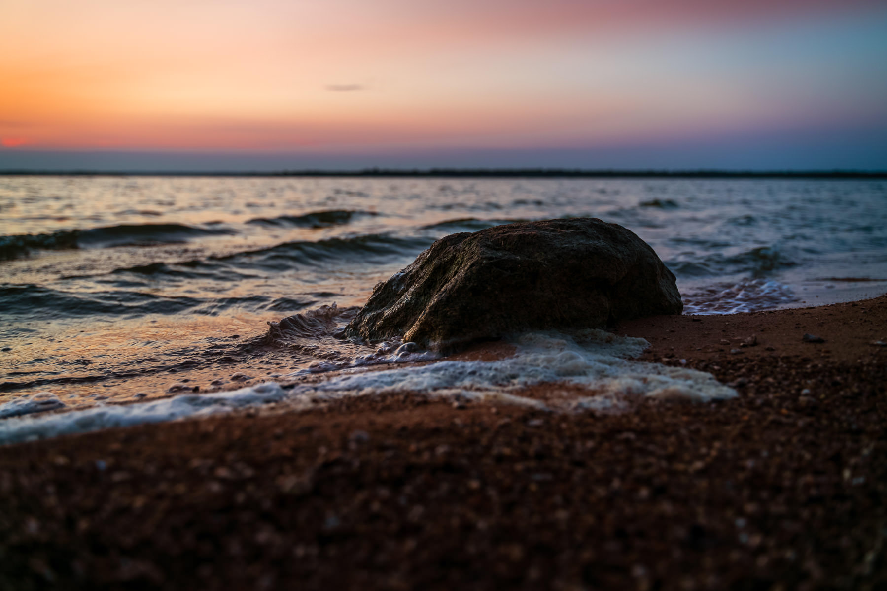Waves gently lap against a rock as the sun rises on Texas' Lake Lavon.