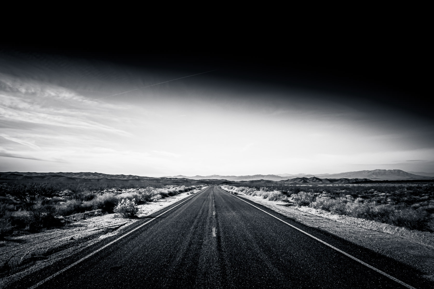 A lonely highway stretches into the desert at the Mojave National Preserve, California.