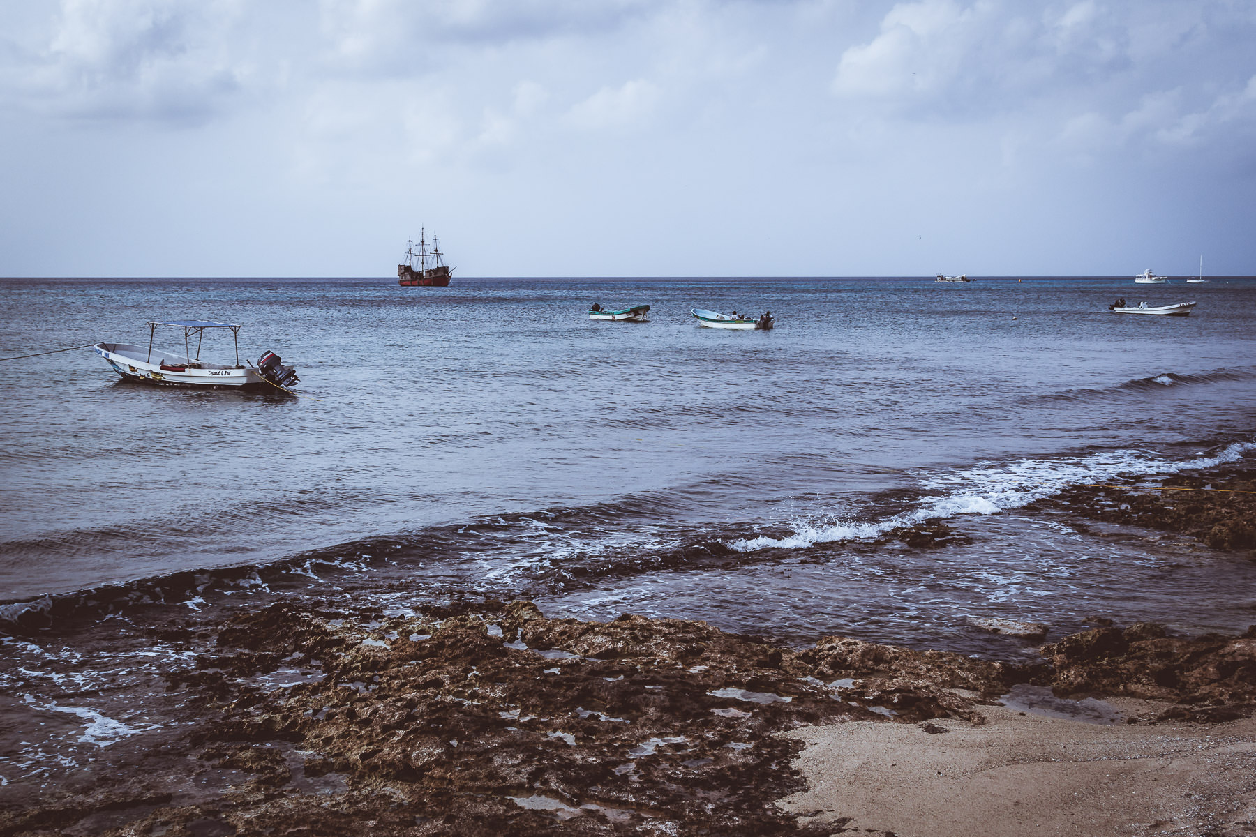 A variety of boats float offshore of the Cozumel, Mexico, beach.