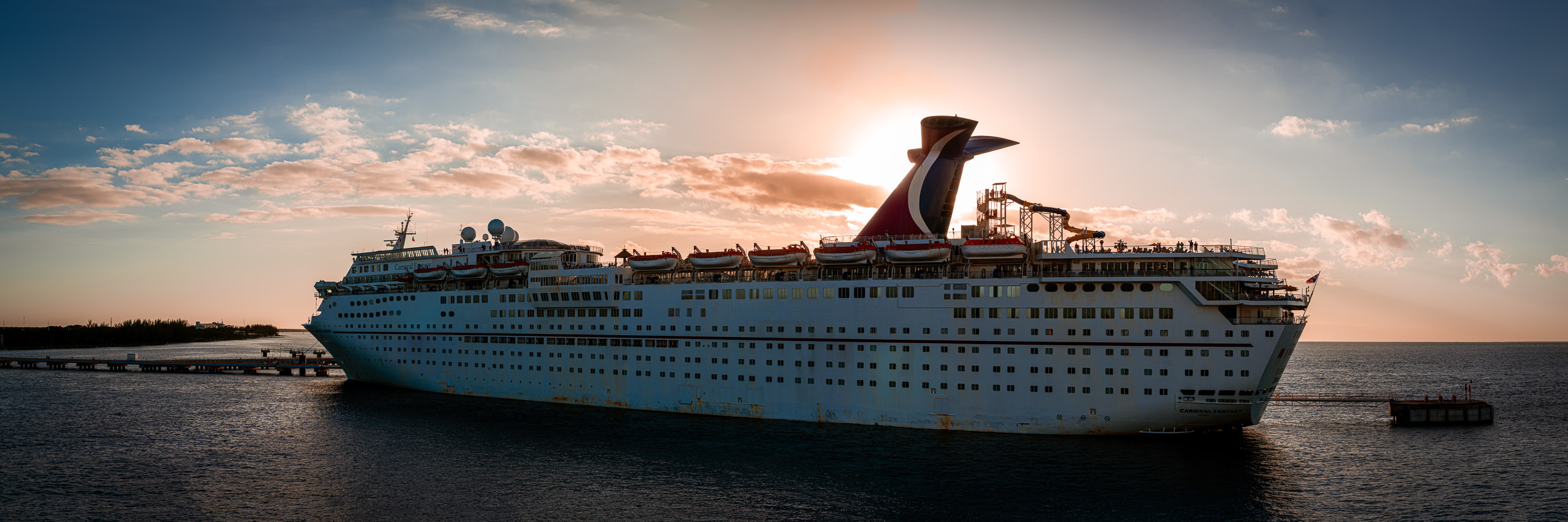 The sun sets behind the cruise ship Carnival Fantasy, docked at Cozumel, Mexico.