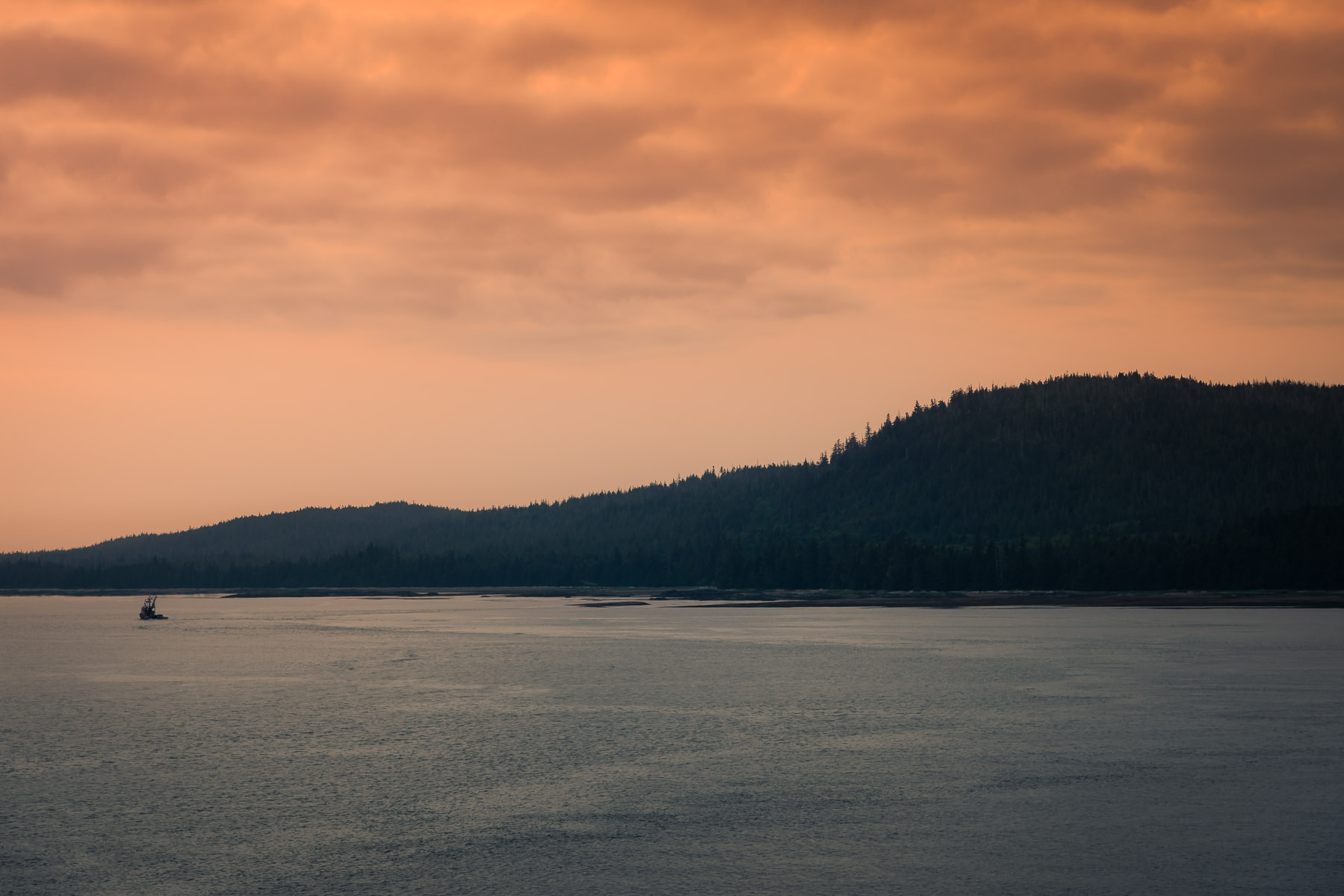 A fishing boat sails the Tongass Narrows as the sun sets on Ketchikan, Alaska.